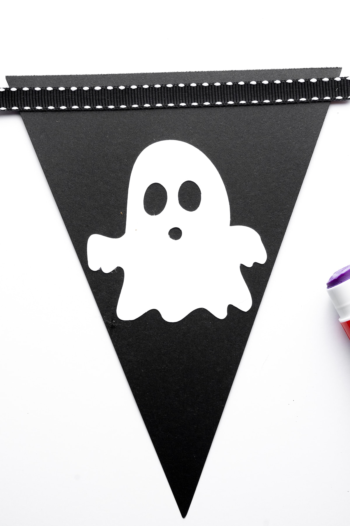 A black bunting triable with cute white cut out ghost with a black and white ribbon across the top, a glue stick is seen peeking in on the side of the image