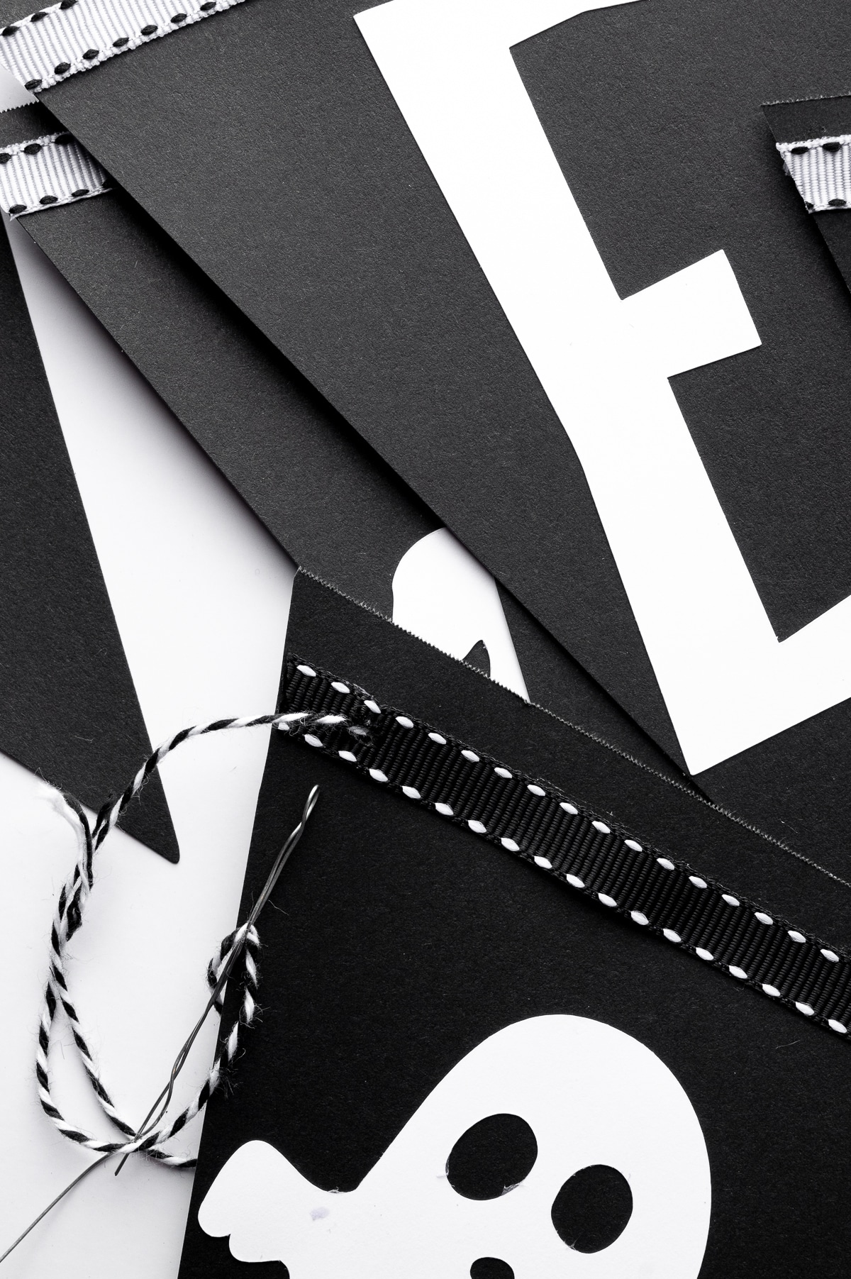 Black bunting triangles with white cut out lettering against a bright white background.  Butchers twine is being weaved through the punched holes
