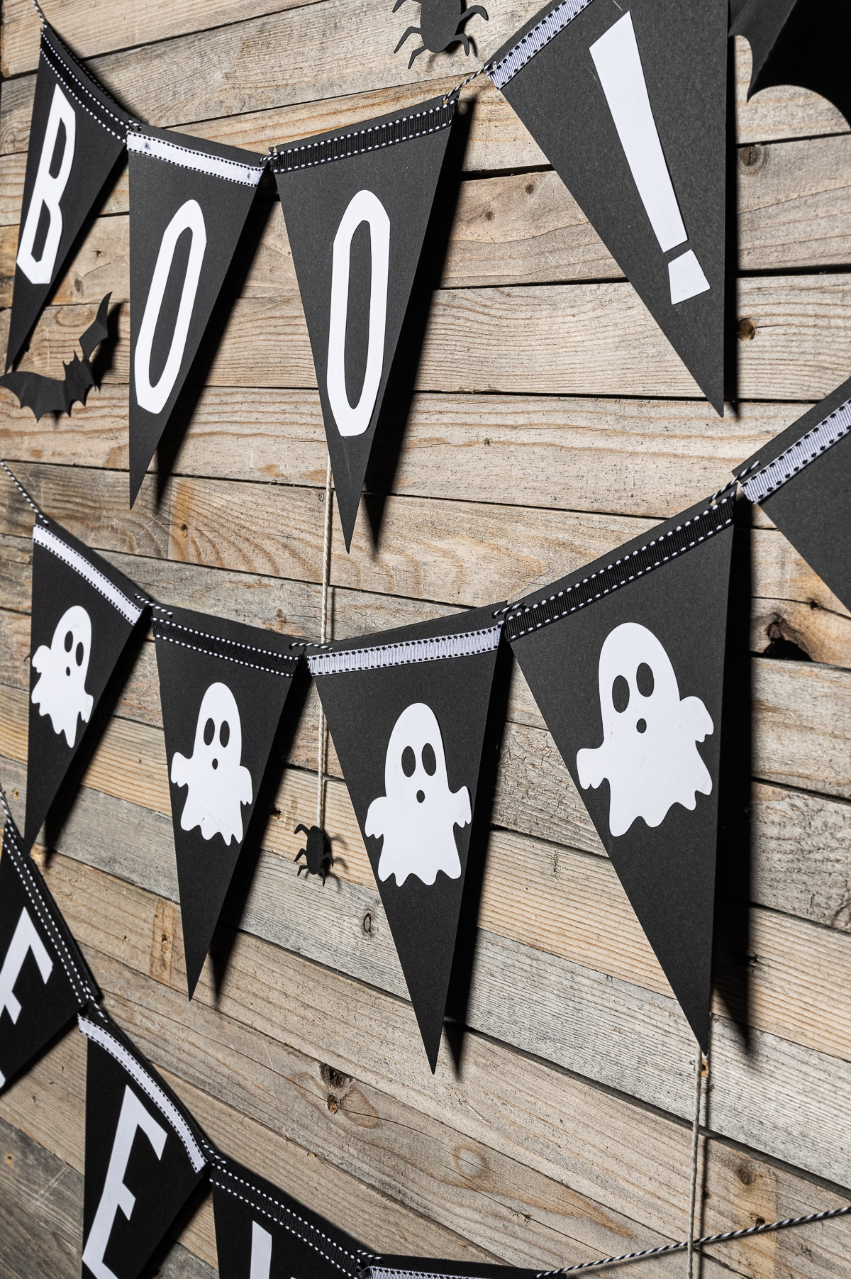 "A black and white Halloween bunting with the phrase ""boo"" visible  The bunting is hanging on a rustic wooden backdrop adorned with paper spiders and bats"