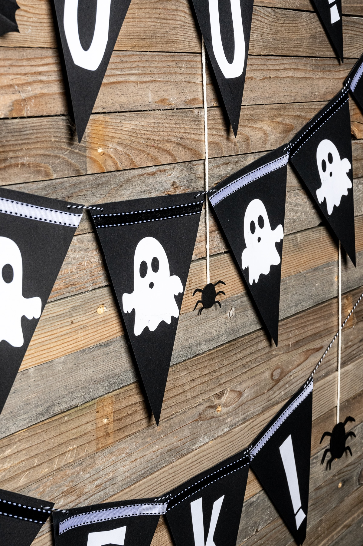 Black bunting with white cut out ghosts on a rustic wooden background