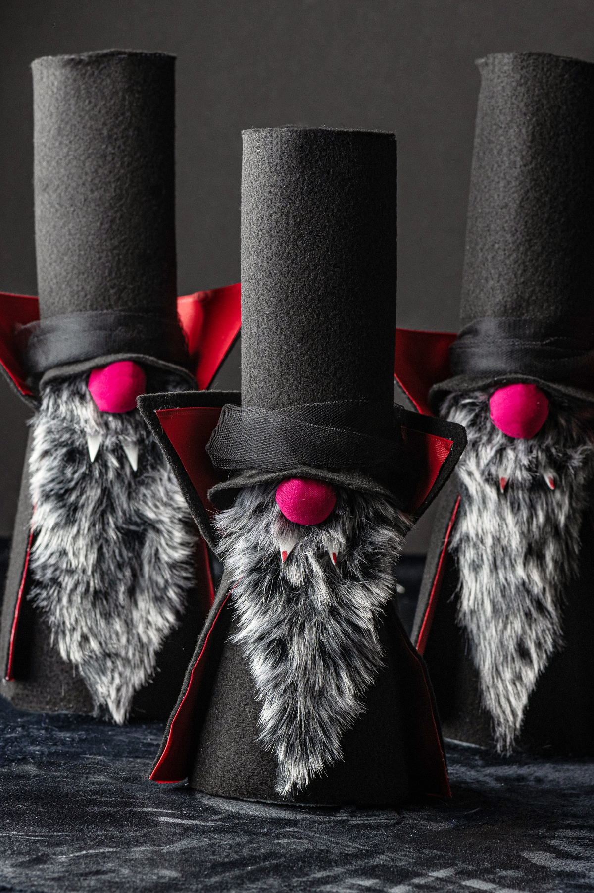 Three felt halloween gnome vampires with tall black hats, and red noses, grey beards and red fangs against a dark black background