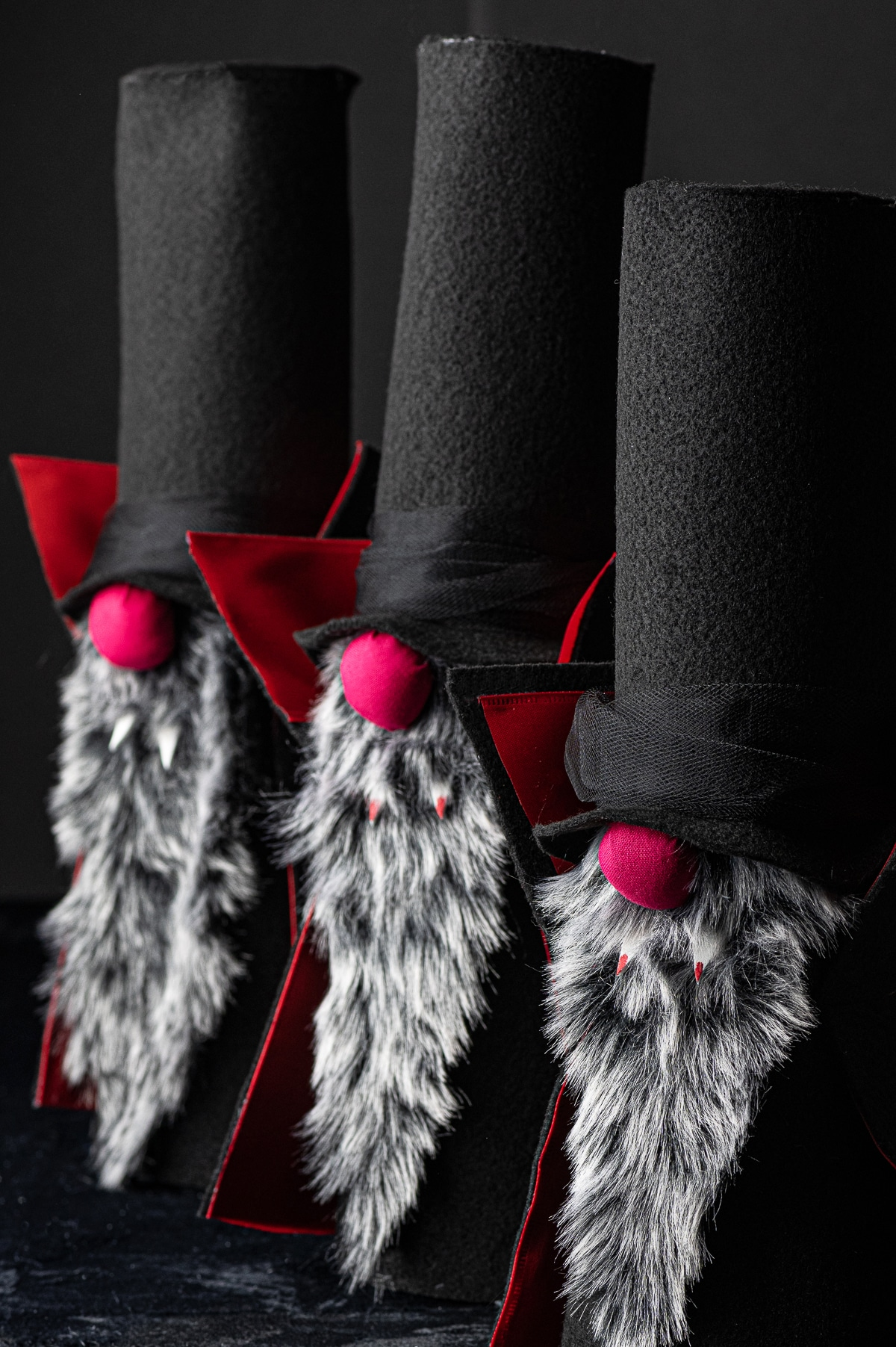Three felt halloween vampire gnomes with tall black hats, and red noses, grey beards and red fangs against a dark black background