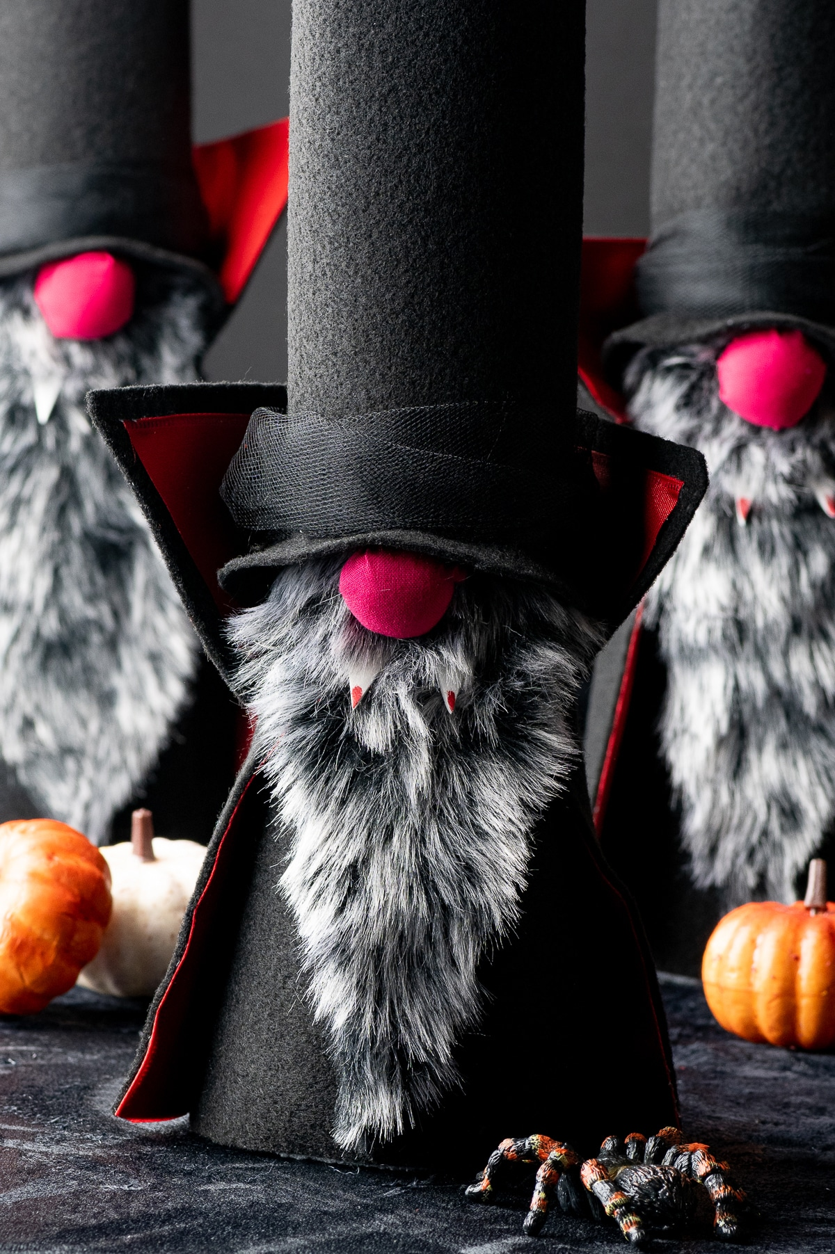 Three felt gnome vampires with tall black hats, and red noses, grey beards and red fangs against a dark black background with mini orange pumpkins and plastic halloween spiders
