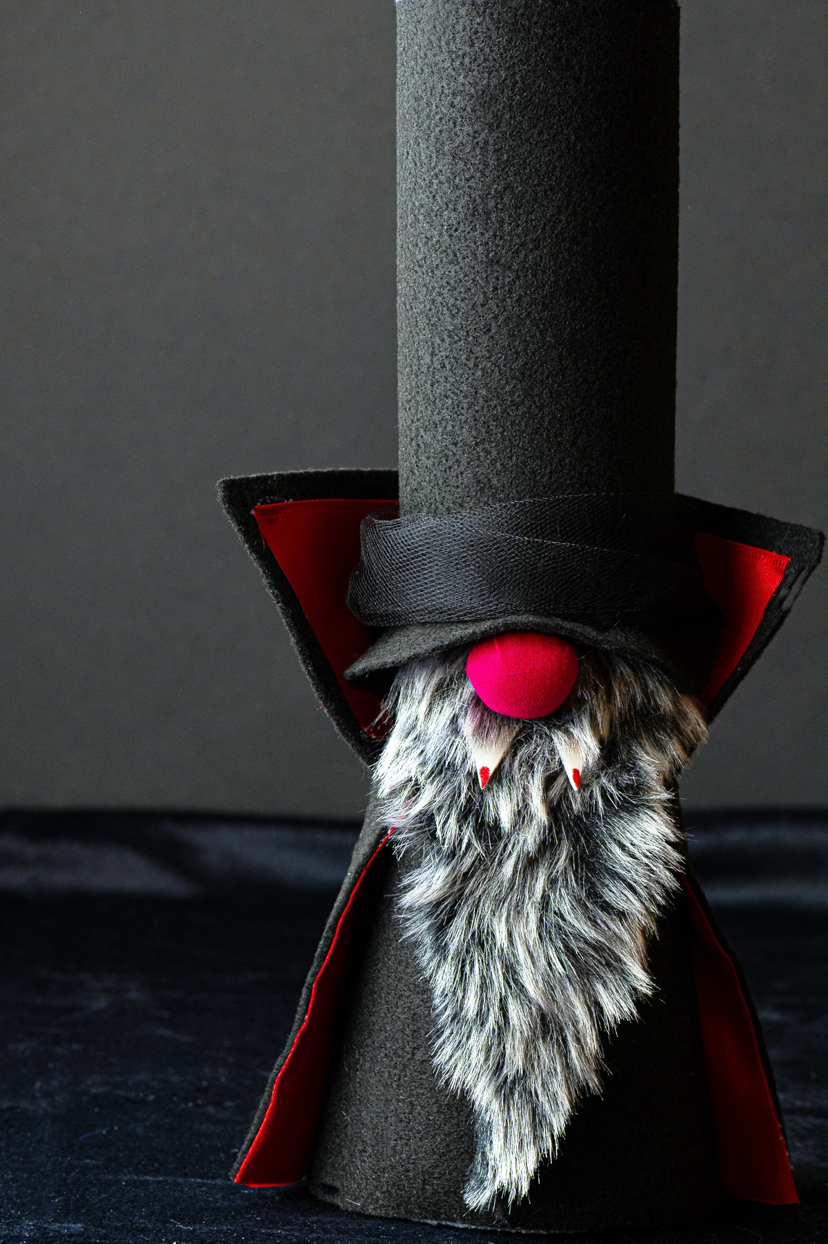 A craft halloween vampire gnome with tall black hat, and red nose, grey beard and red fangs against a dark black background