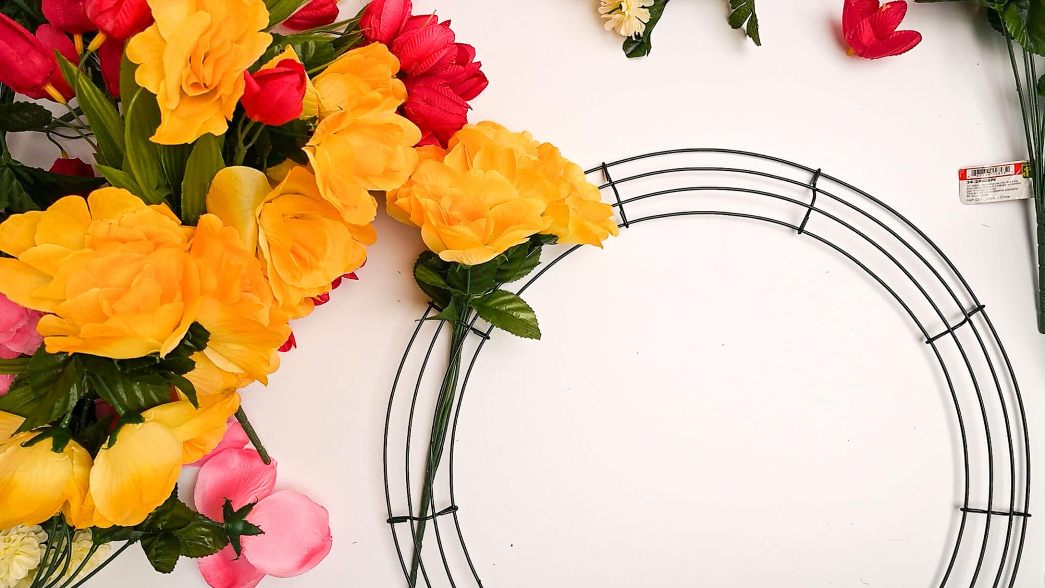 A wire wreath form with a single bundle of fake flowers placed through the centre wire.   Bundles of fresh flowers sit beside the wreath form.