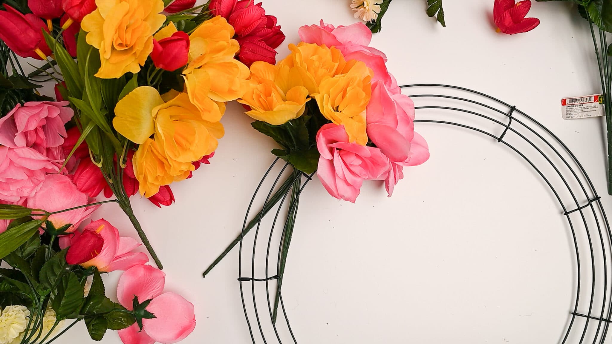 A wire wreath form with three bundles of fake flowers placed through the centre wire.   Bundles of fresh flowers sit beside the wreath form.
