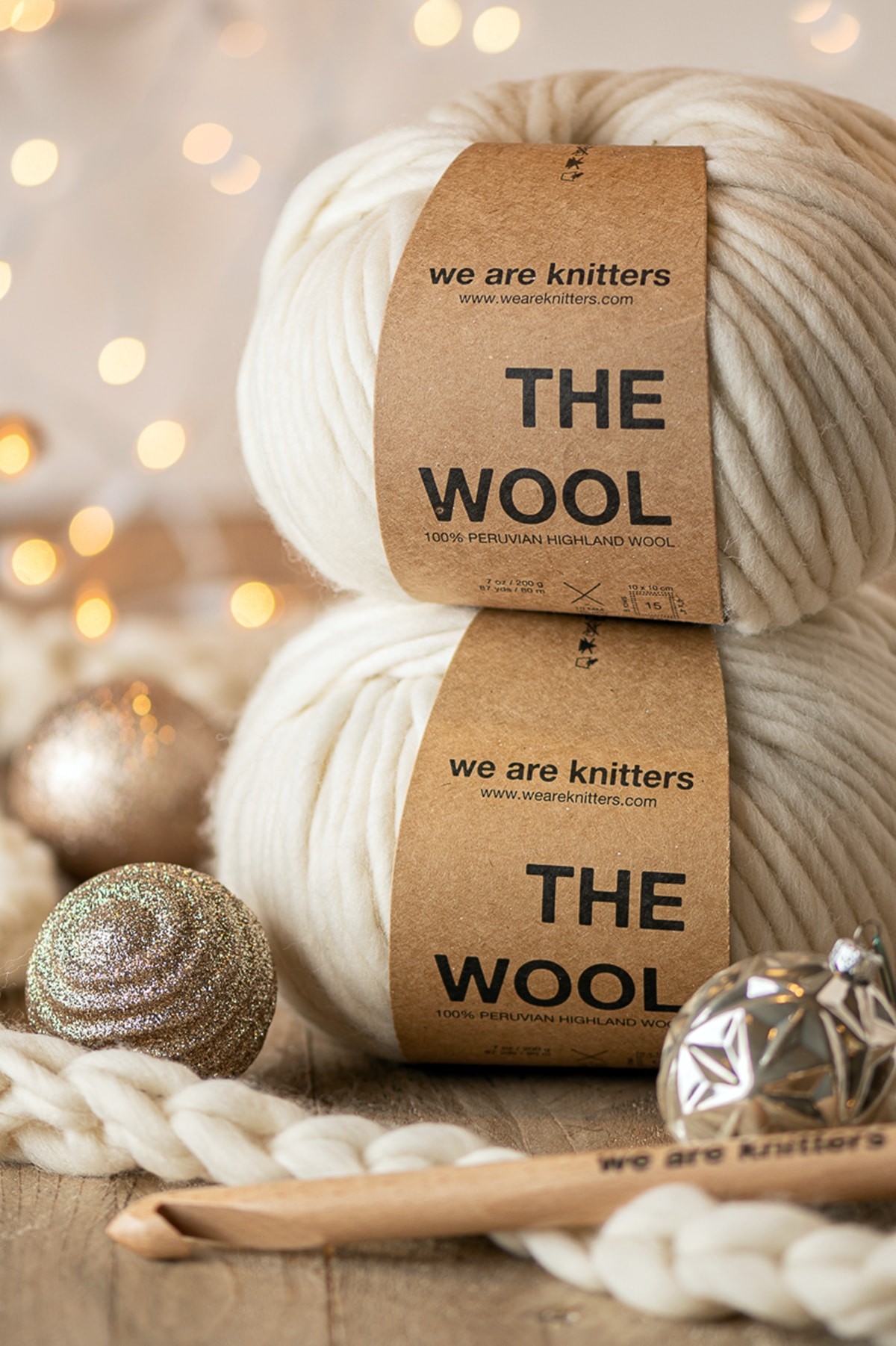 Two skeins of cream colored bulk wool stacked on top of each other surrounded by holiday ornaments, a wooden crochet hook and yellow twinkle lights in the background.