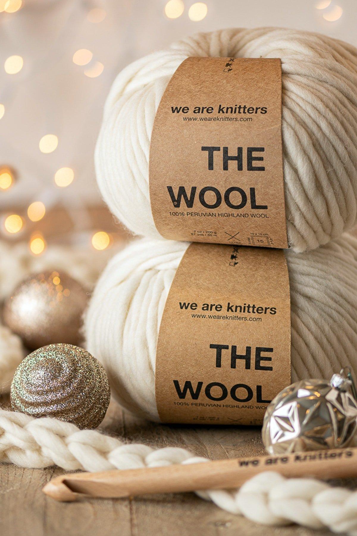 Zwei Stränge cremefarbener Wolle übereinander gestapelt, umgeben von Weihnachtsornamenten, einer hölzernen Häkelnadel und gelben funkelnden Lichtern im Hintergrund.