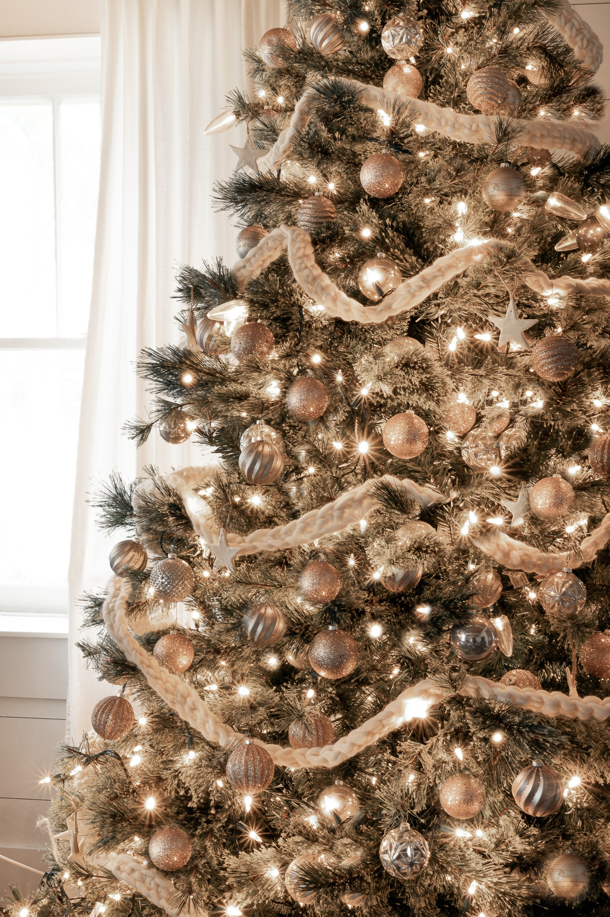 Monochrome Christmas tree with gold and silver ornaments and bright yellow white lights with a  cream colored homemade crochet garland.