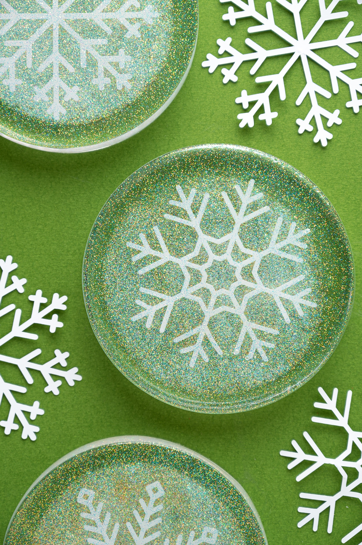 Round resin epoxy coasters with white snowflake cutouts and prismatic glitter on a green background