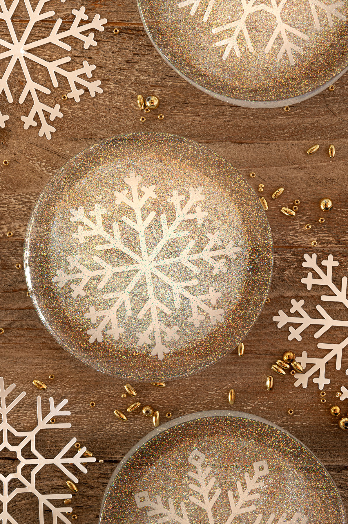 Round resin epoxy coasters with white snowflake cutouts and prismatic glitter on a rustic wooden background surrounded by gold beads of different colors.