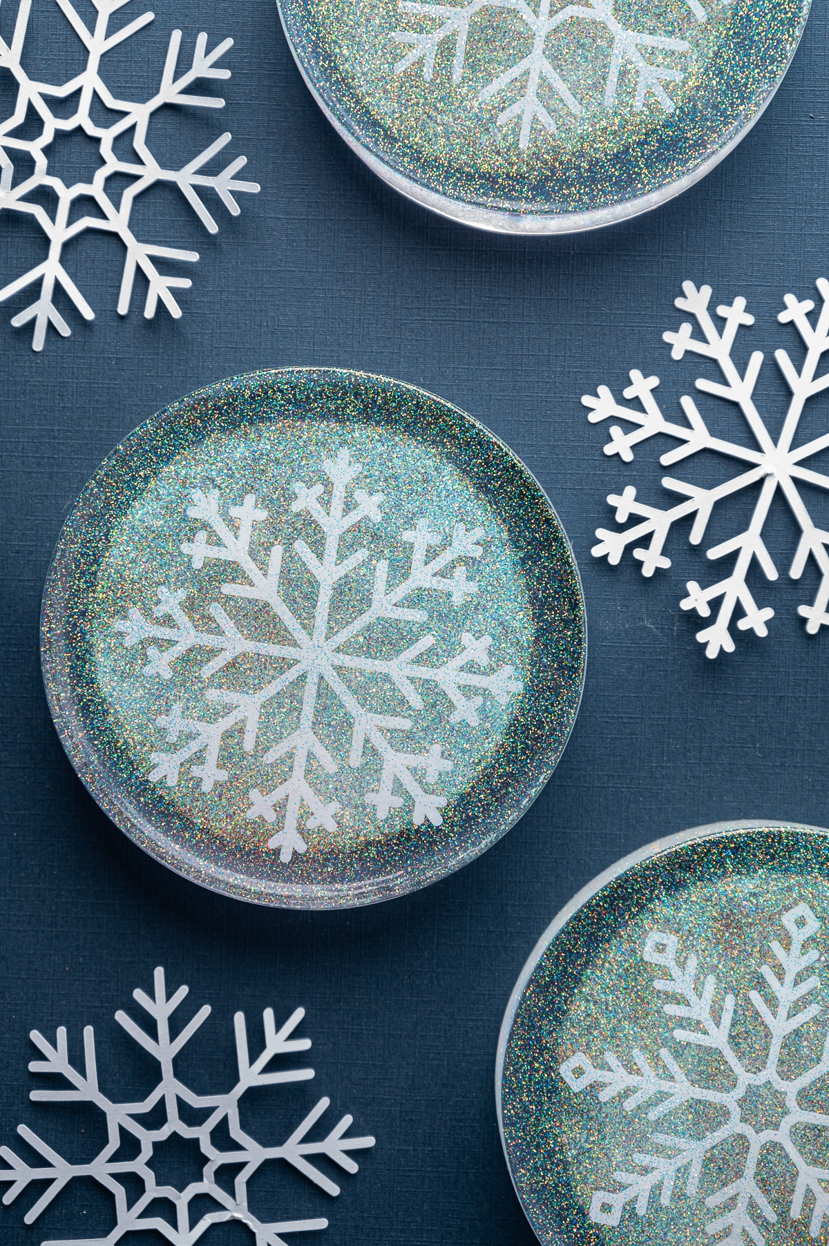 Round resin epoxy coasters with white snowflake cutouts and prismatic glitter on a dark blue background