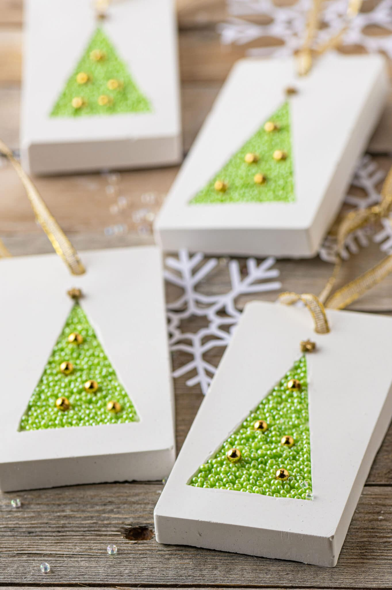 Handmade gift tag made from plaster and inlayed with small green beads.  Surrounded by white paper snowflakes and clear glass beads