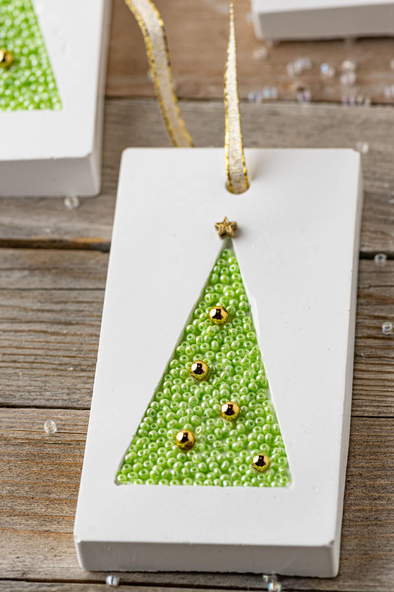 Handmade gift tag made from plaster and inlayed with small green beads.