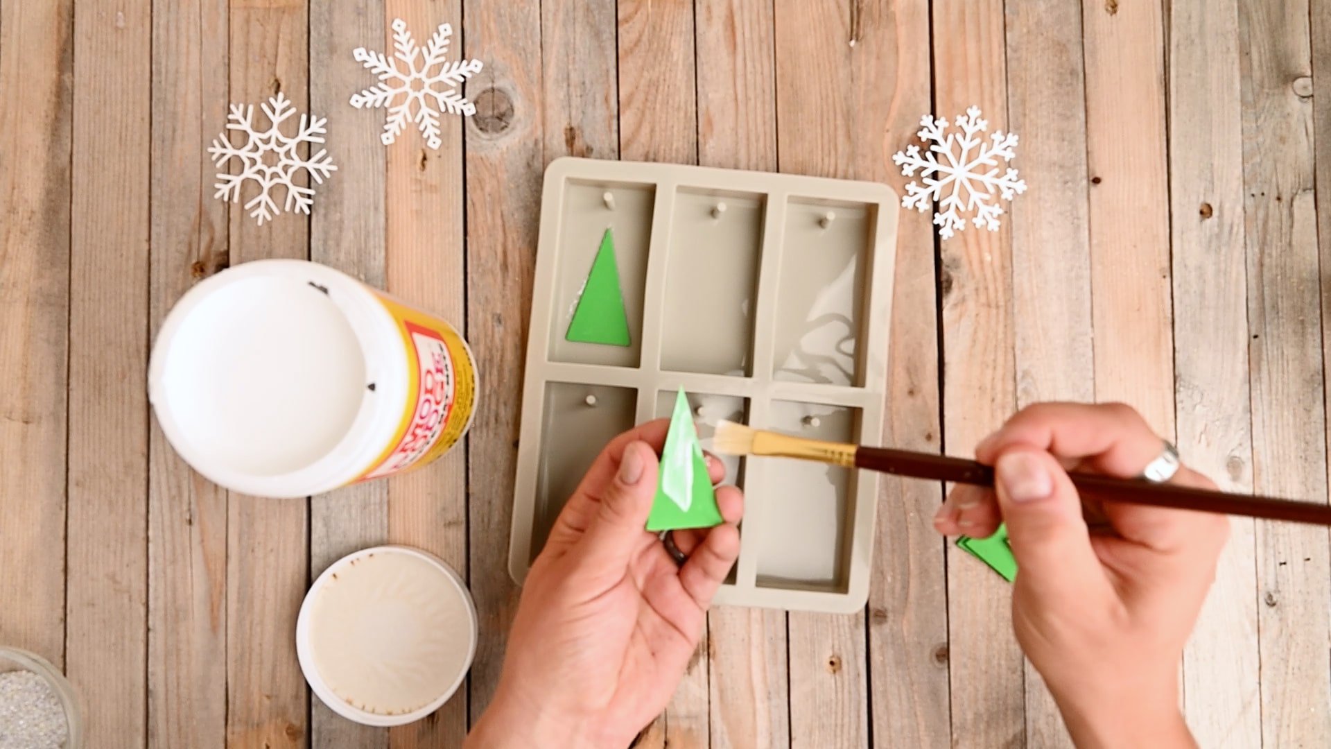 Use a paintbrush to coat one side of each triangle with glue. Stick them down inside the molds.