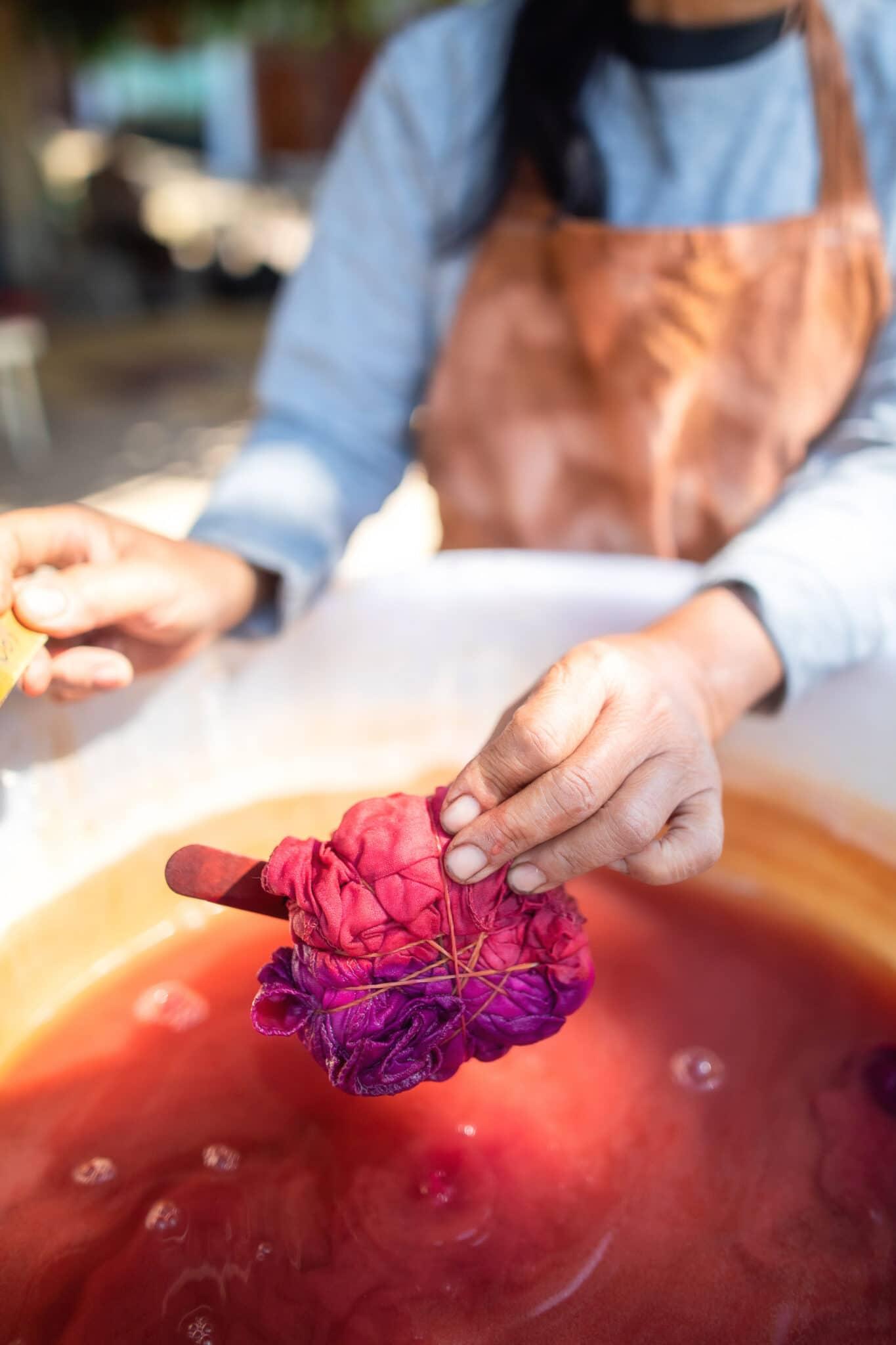 Ein Stoffbündel nach dem Eintauchen in rosa Farbstoff.