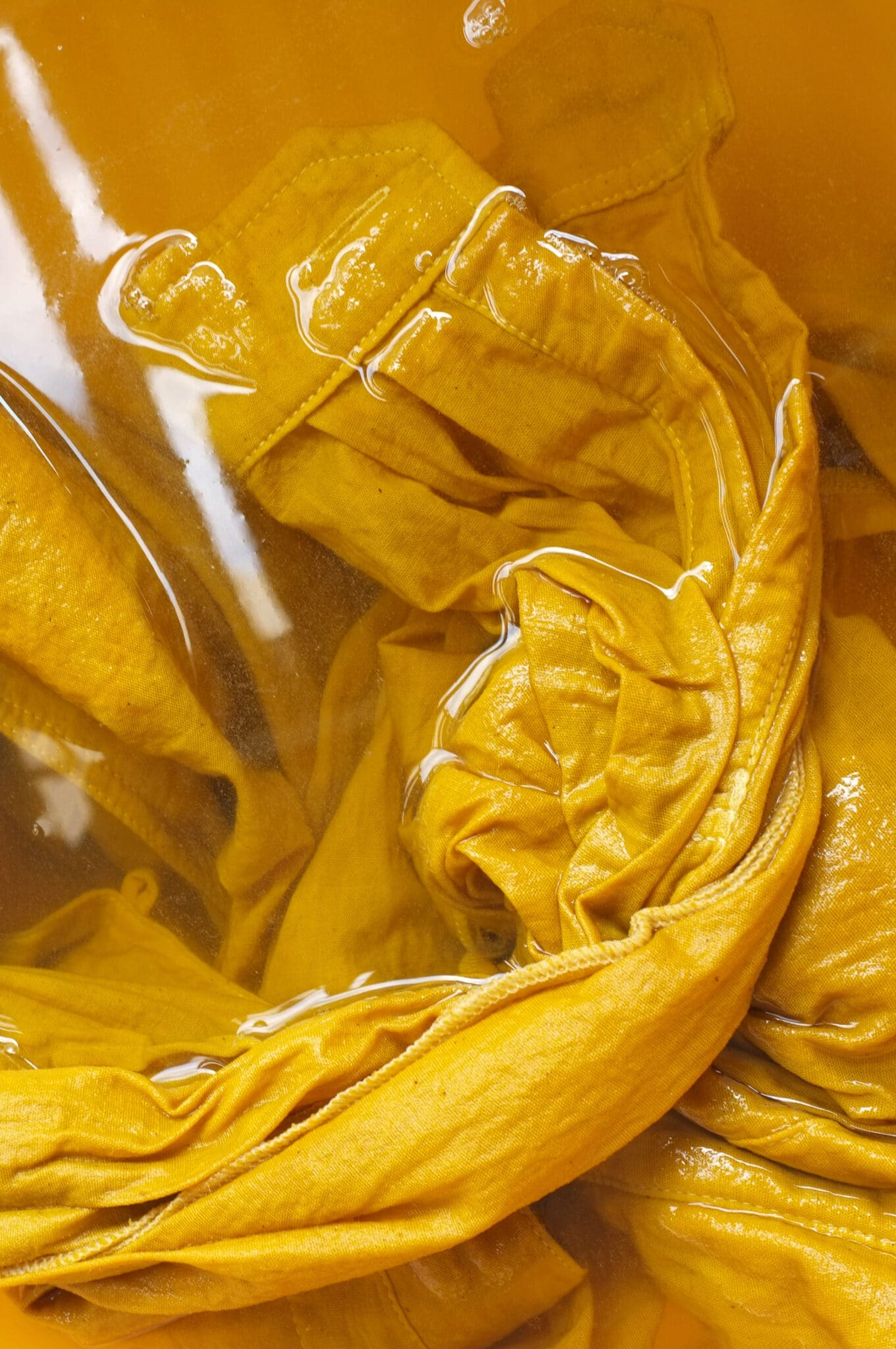 Gelber Stoff, der in einem Färbebad eingeweicht wird.