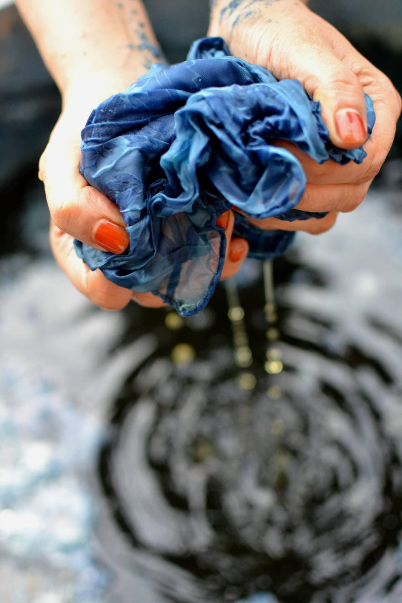 Blauer Farbstoff wird von Hand aus dem Stoff gepresst.