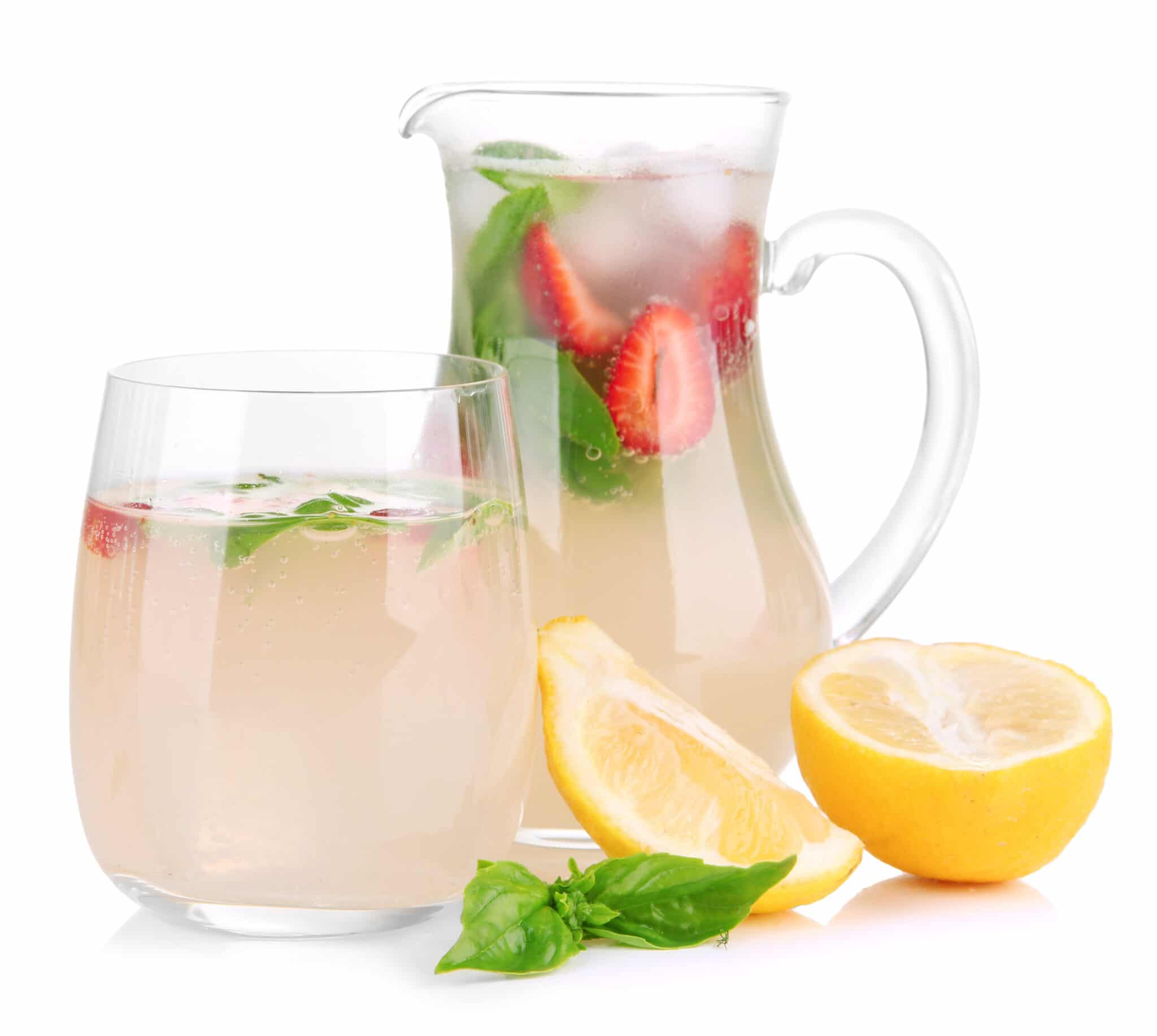 A glass and jug of light pink lemonade infused with strawberries, basil and fresh lemon.  Lemon wedges and basil can be seen on the table in front of the jug.