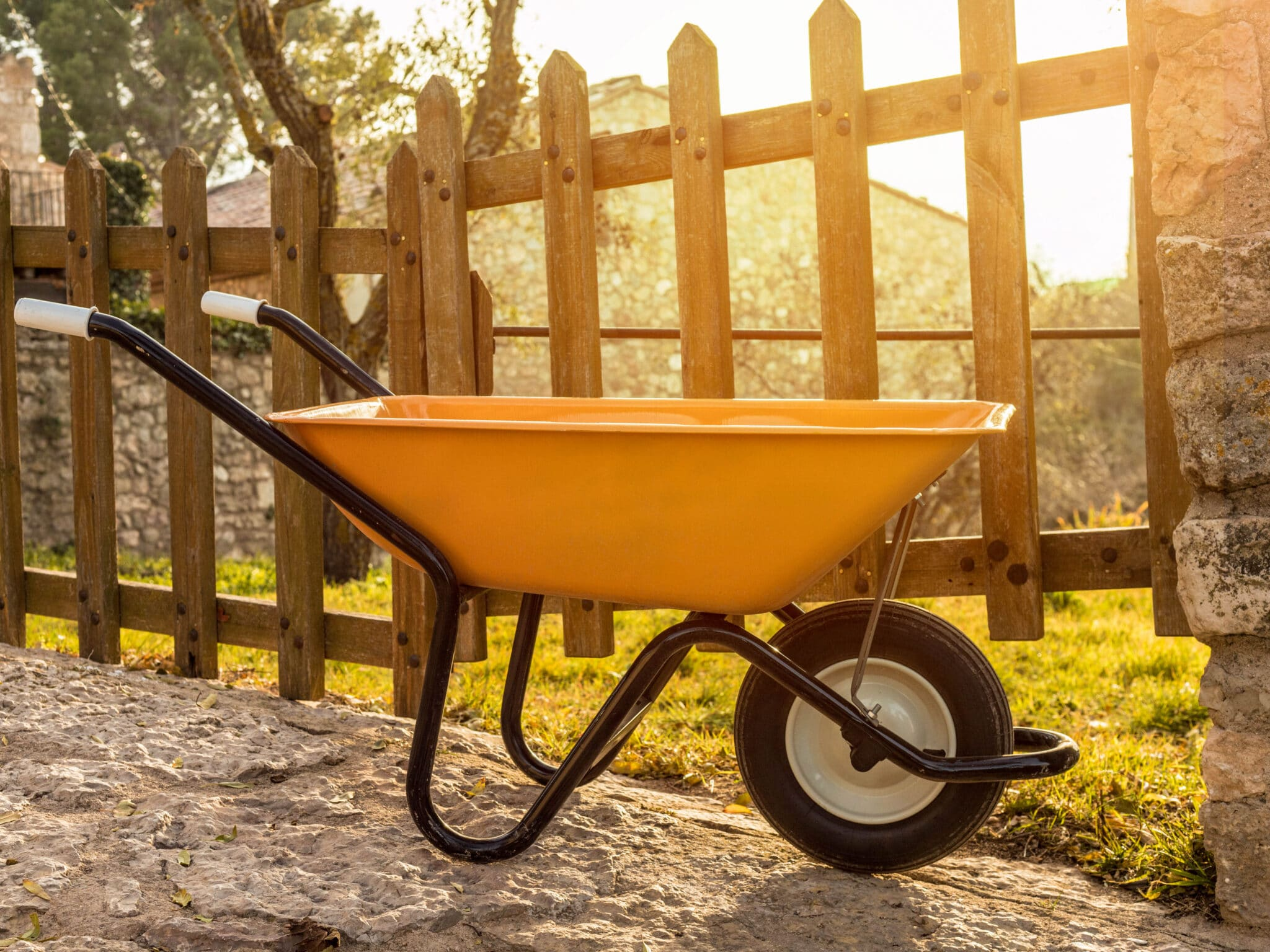 A little yellow wheelbarrow parked beside a picket fence on a stone path.