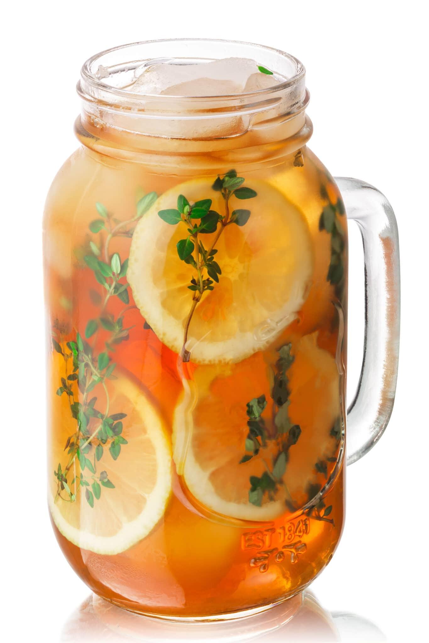 Iced thyme lemon tea in a mason jar, isolated