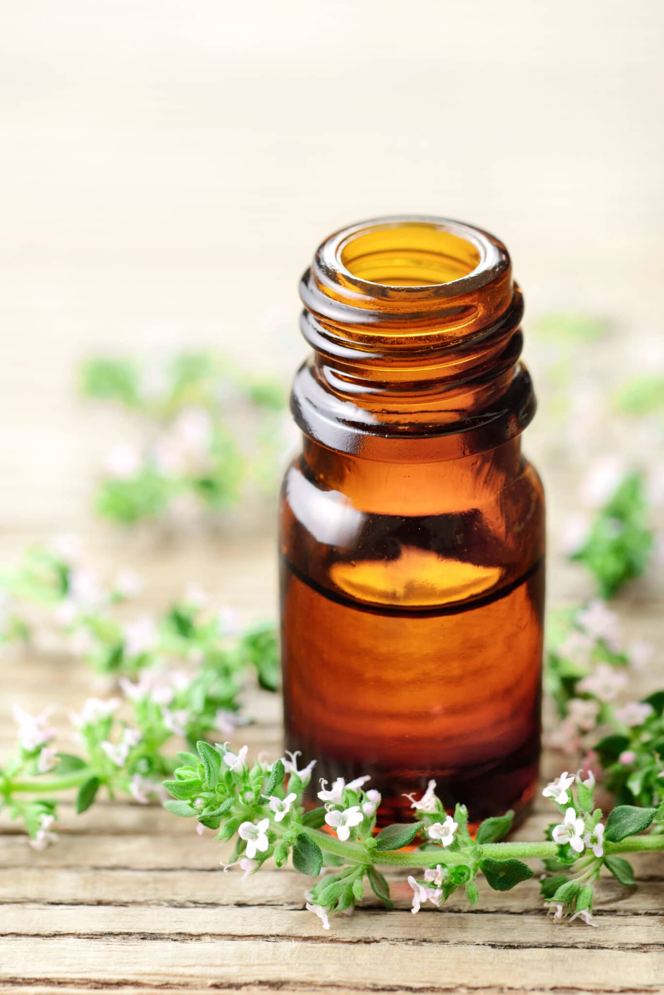 Thyme essential oil in the glass bottle, with thyme flowers