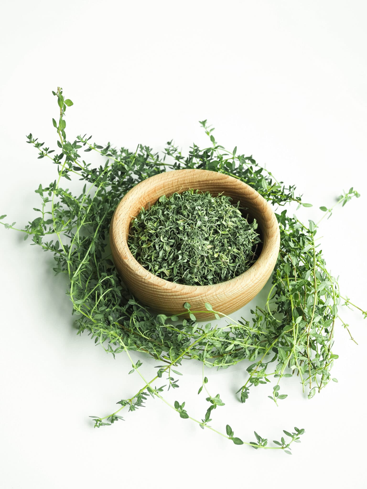Wooden bowl of dry thyme on white background.