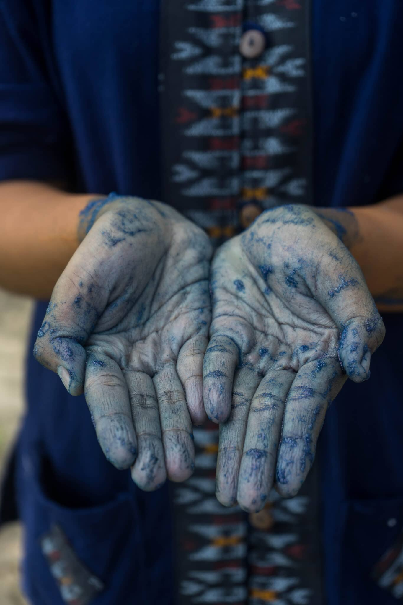 A fabric dyer's hands stained blue with natural dyes.