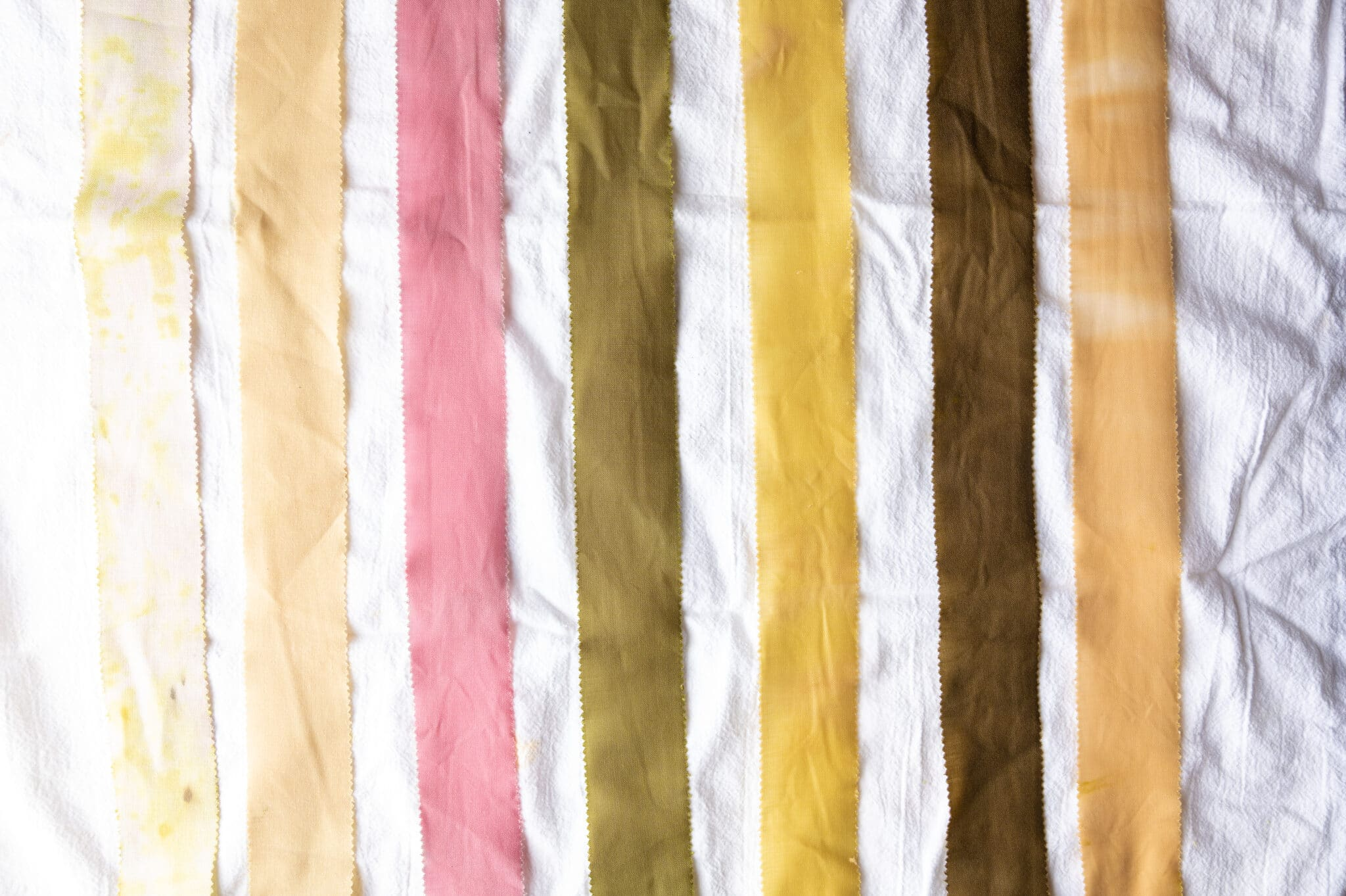 Seven strips of fabric that were dyed using natural dye made from onion skins. Each strip is a different shade, ranging from brown to yellow to pink.