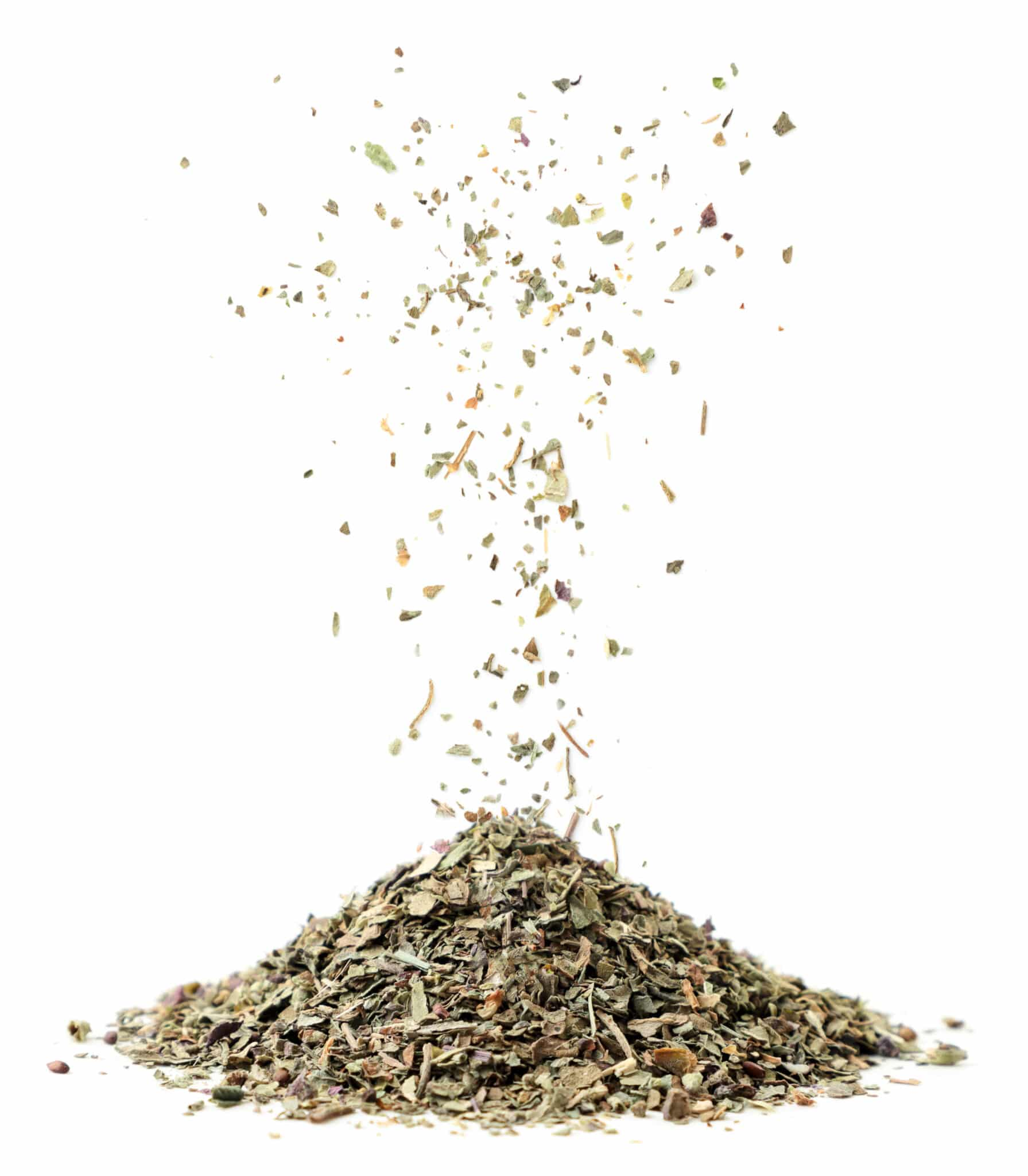 Dried Basil being sprinkled into a mound against a bright white background.