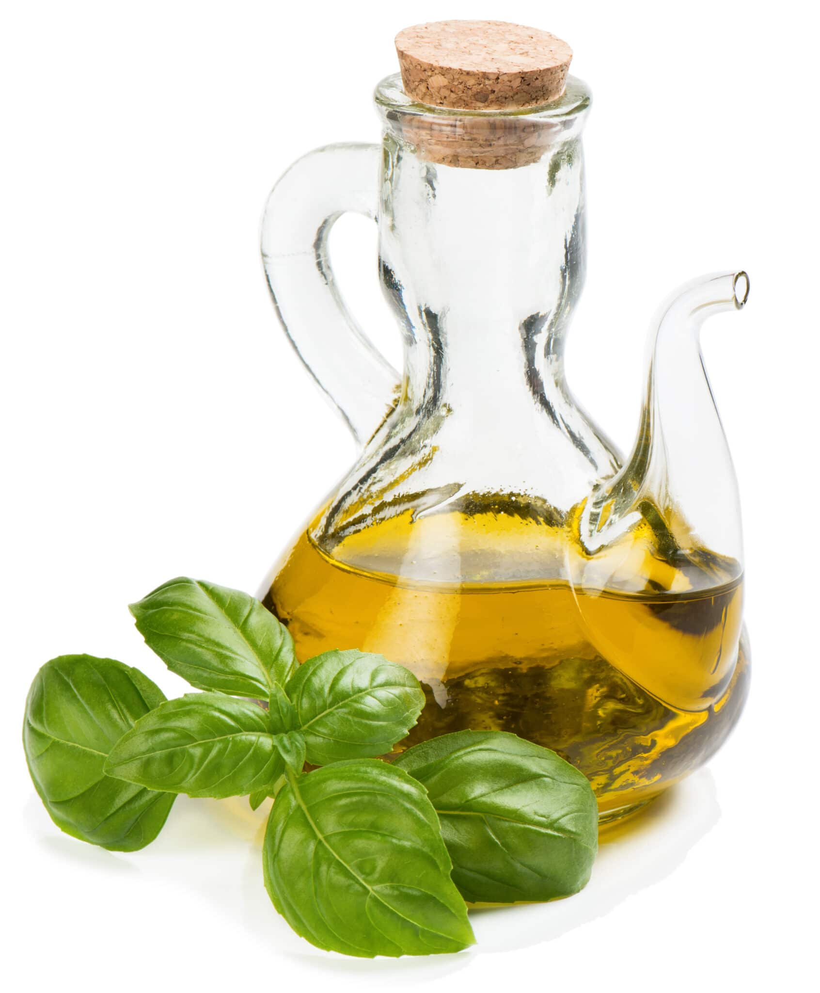 A jar of infused olive oil with a sprig of fresh basil against a bright white background.