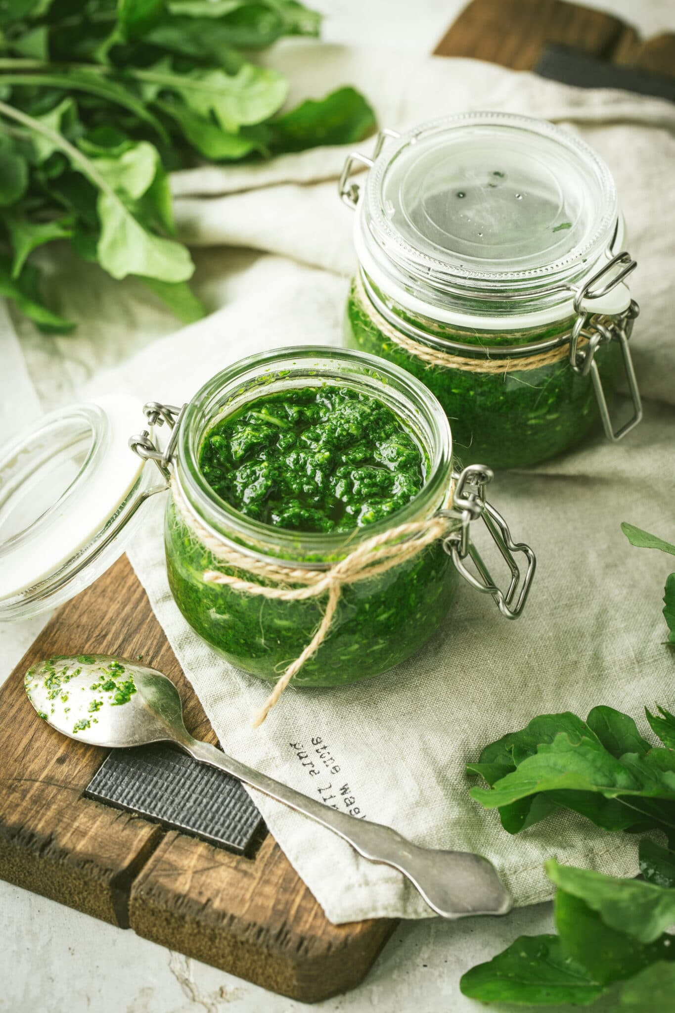 Jars of bright green homemade pest on a  rustic wooden cutting board with a linen napkin.  Fresh basil can be seen in the background.