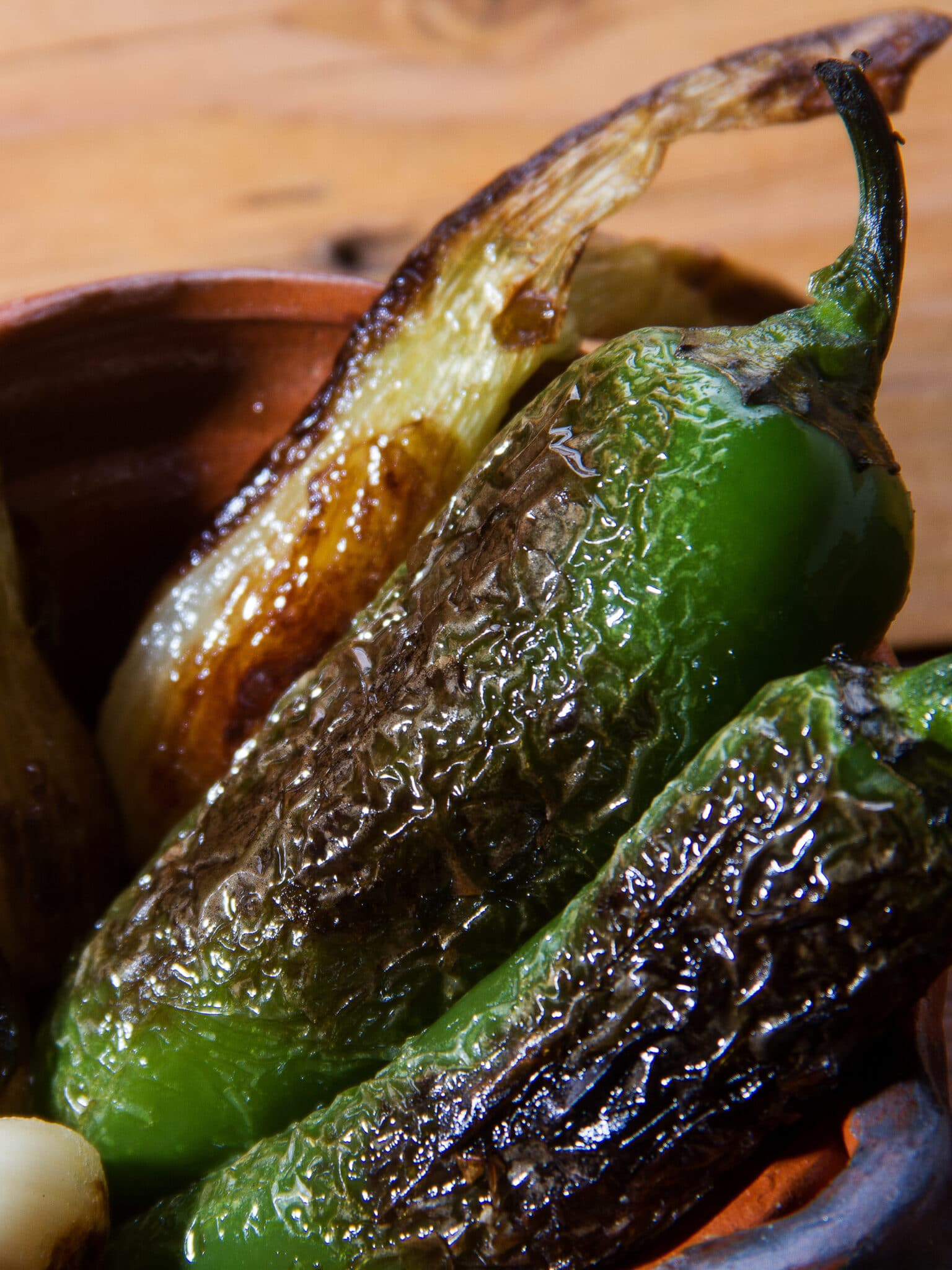 Jalapenos in a bowl, roasted until their skin blackened.