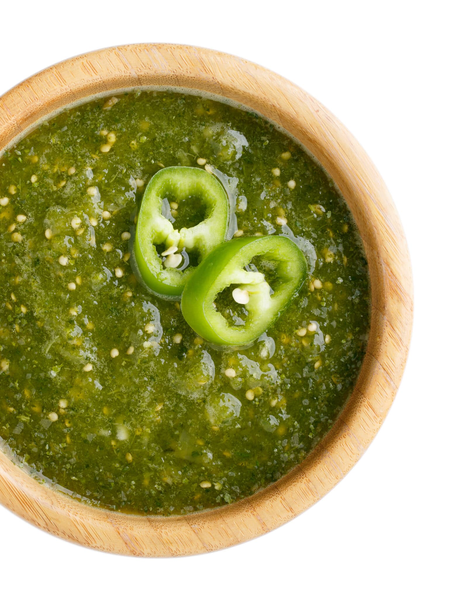A bowl of green hotsauce with jalapeno slices.