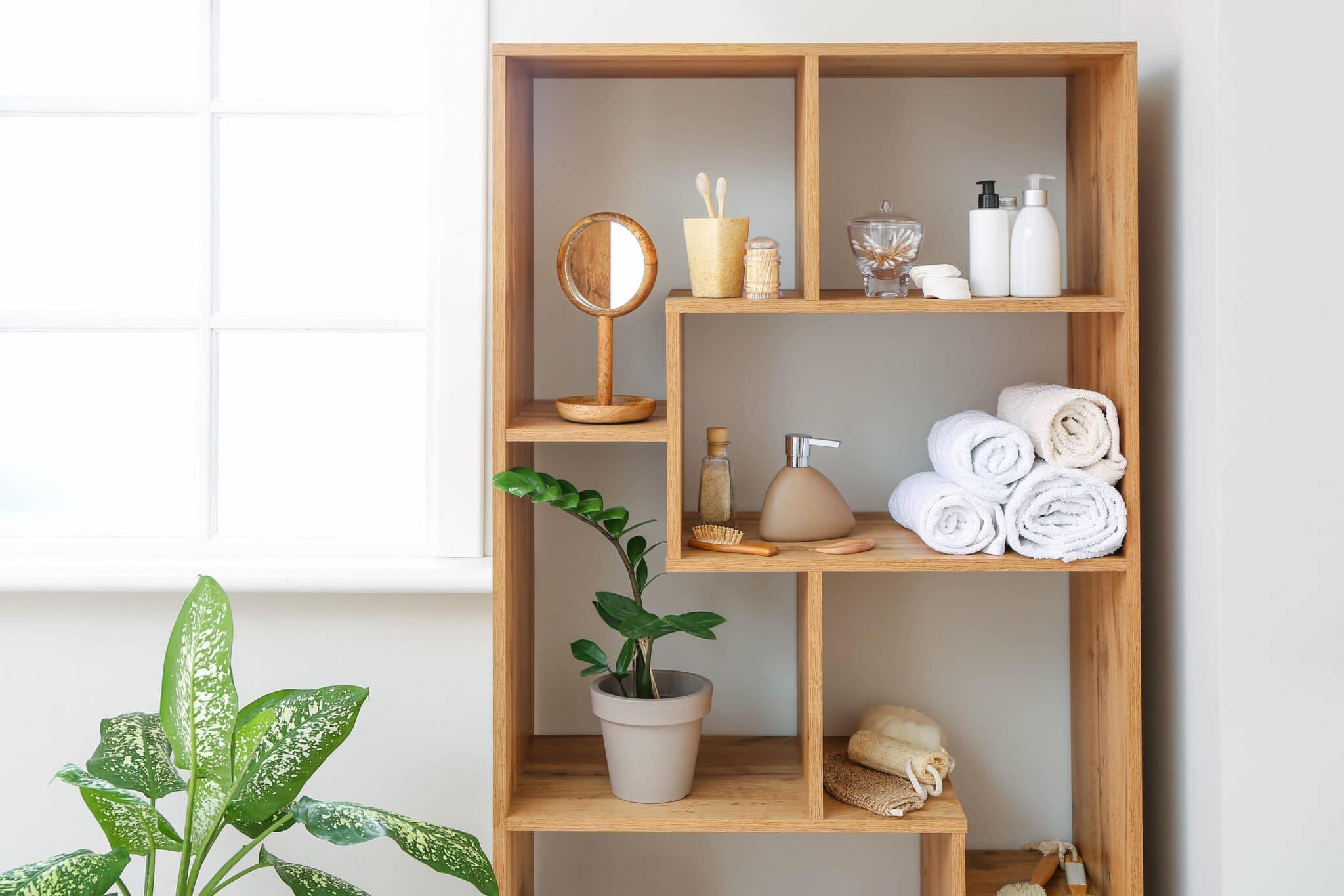 Un meuble en bois servant de rangement dans une petite salle de bain.