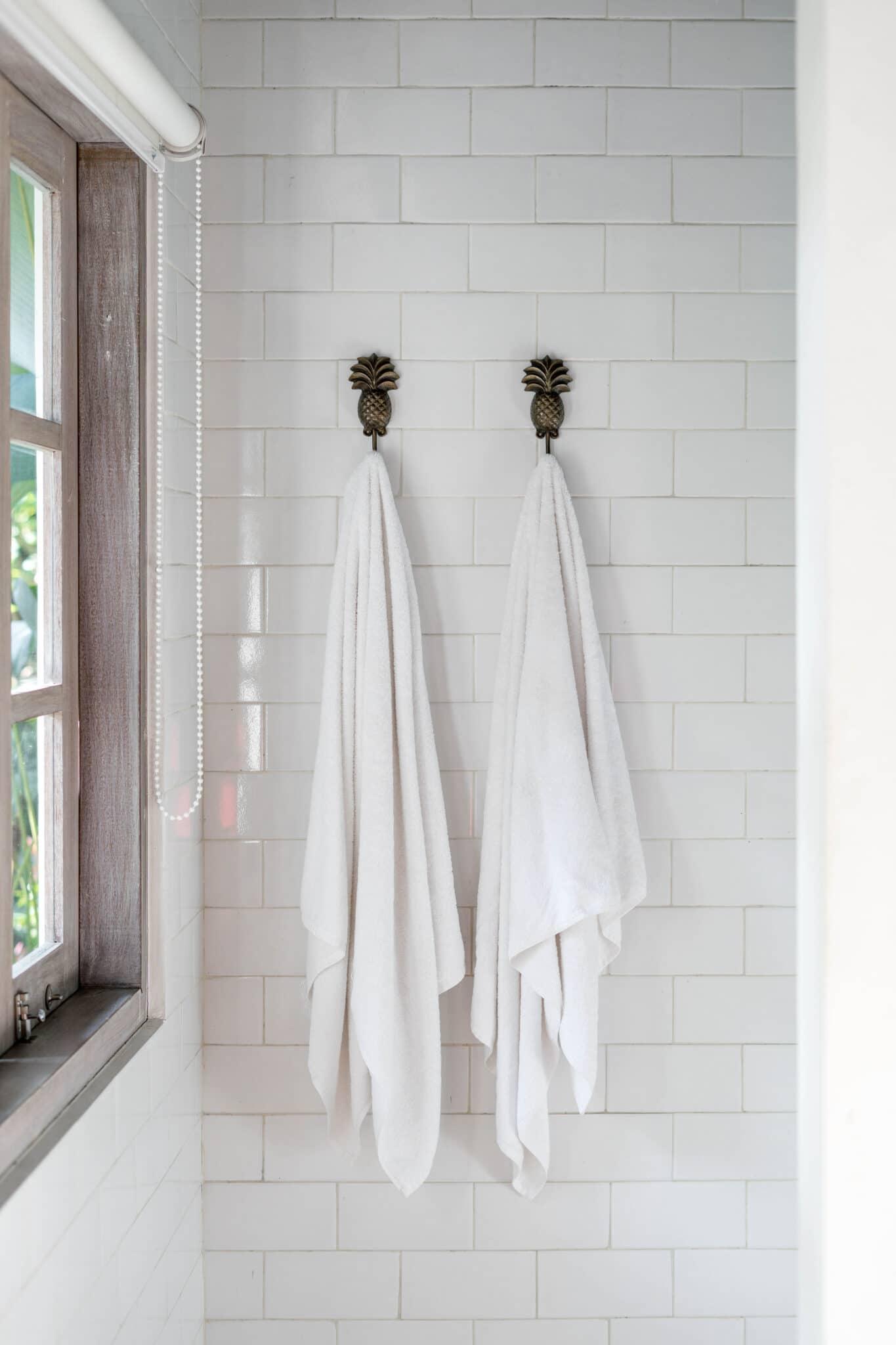 Serviettes de bain suspendues à des crochets dans une petite salle de bain pour gagner de la place.