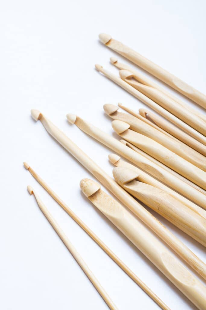 Different sized wooden crochet hooks against a bright white background.