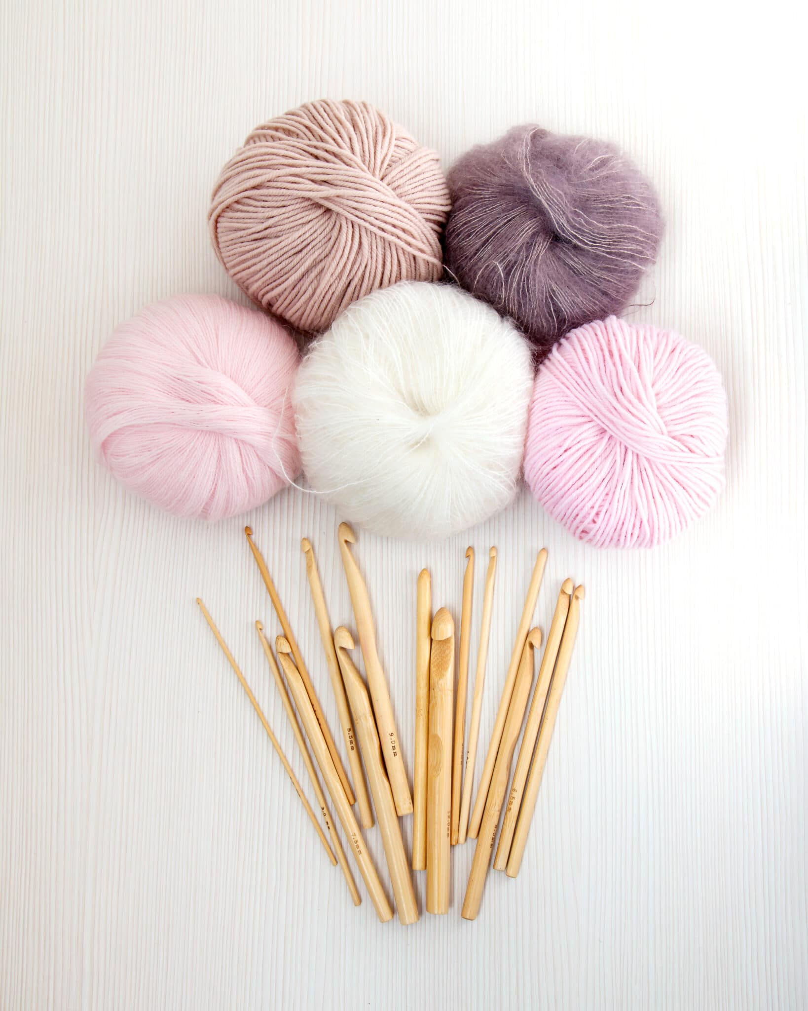 Wooden crochet hooks on white wood background with balls of yarn pastel colors. Top view. Hobby and handmade concept.