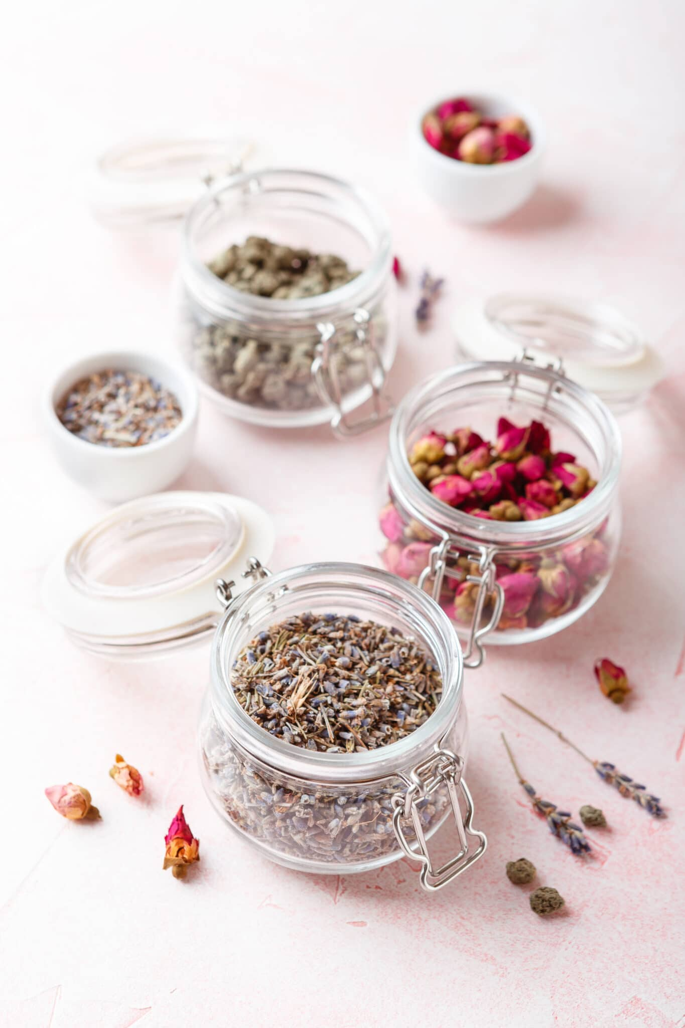 Dried rose flower buds and flowers in glass jars.
