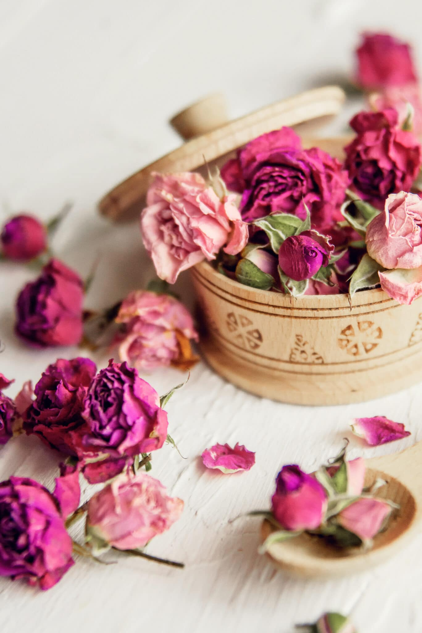 Rose potpourri in a small wooden covered bowl against a rustic white wooden table top.
