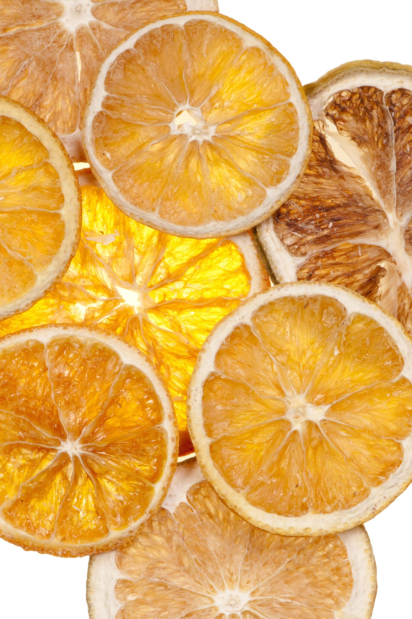Dried orange slices against a bright white table top.