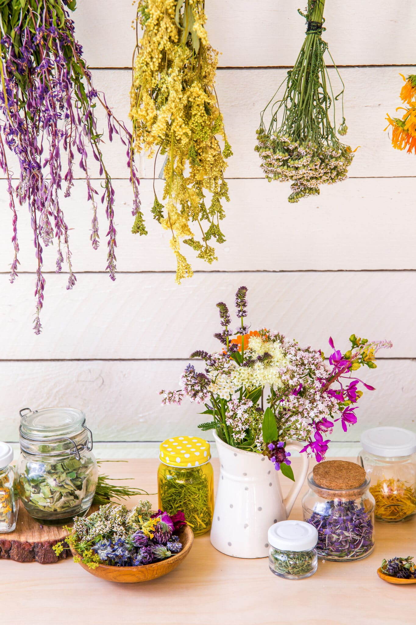 Dried flowers and herbs in jars on a wooden tabletop framed with hanging dried colourful flower bundles.