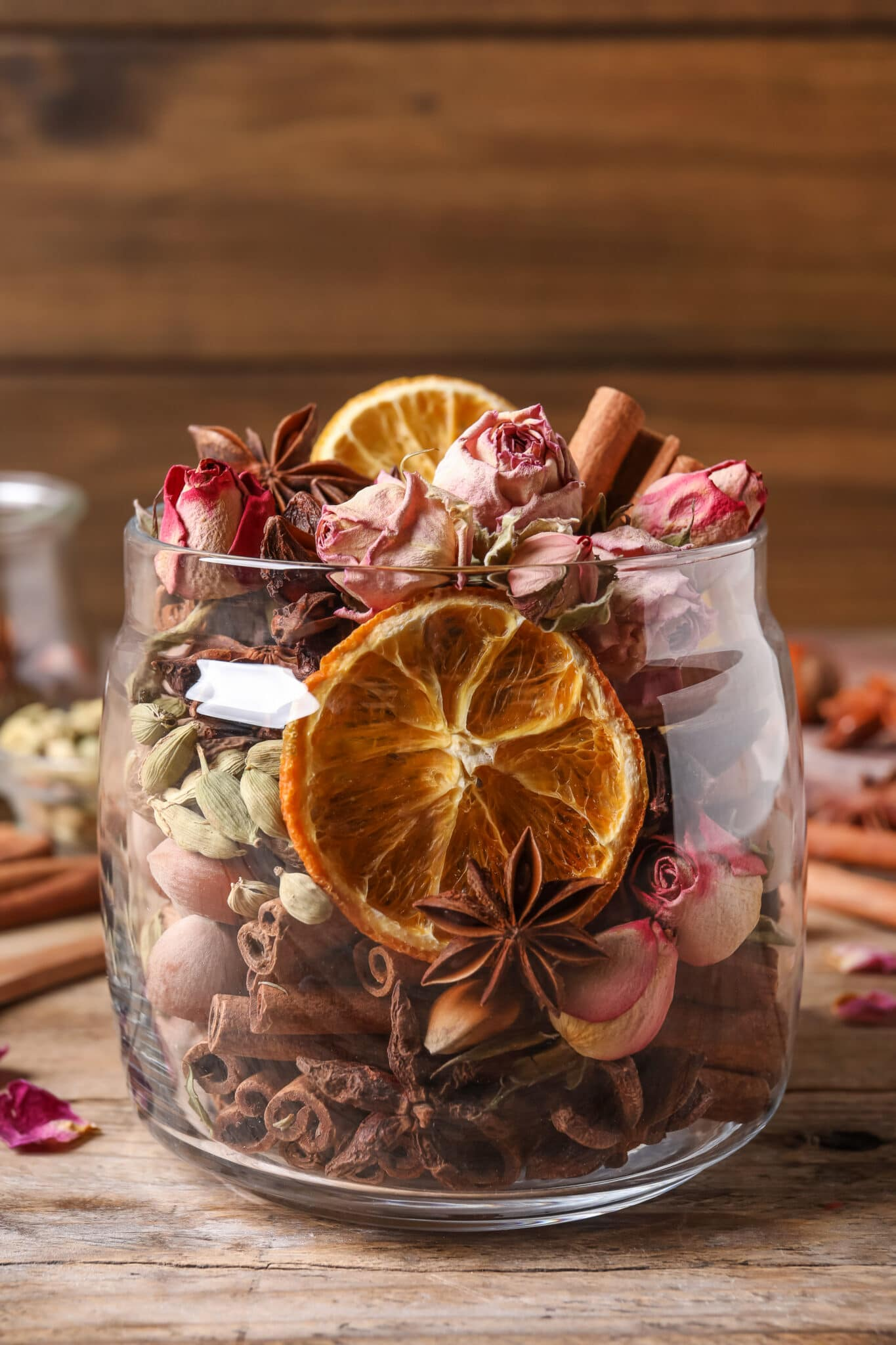Spicy potpourri in a glass jar against a rustic wooden backdrop.