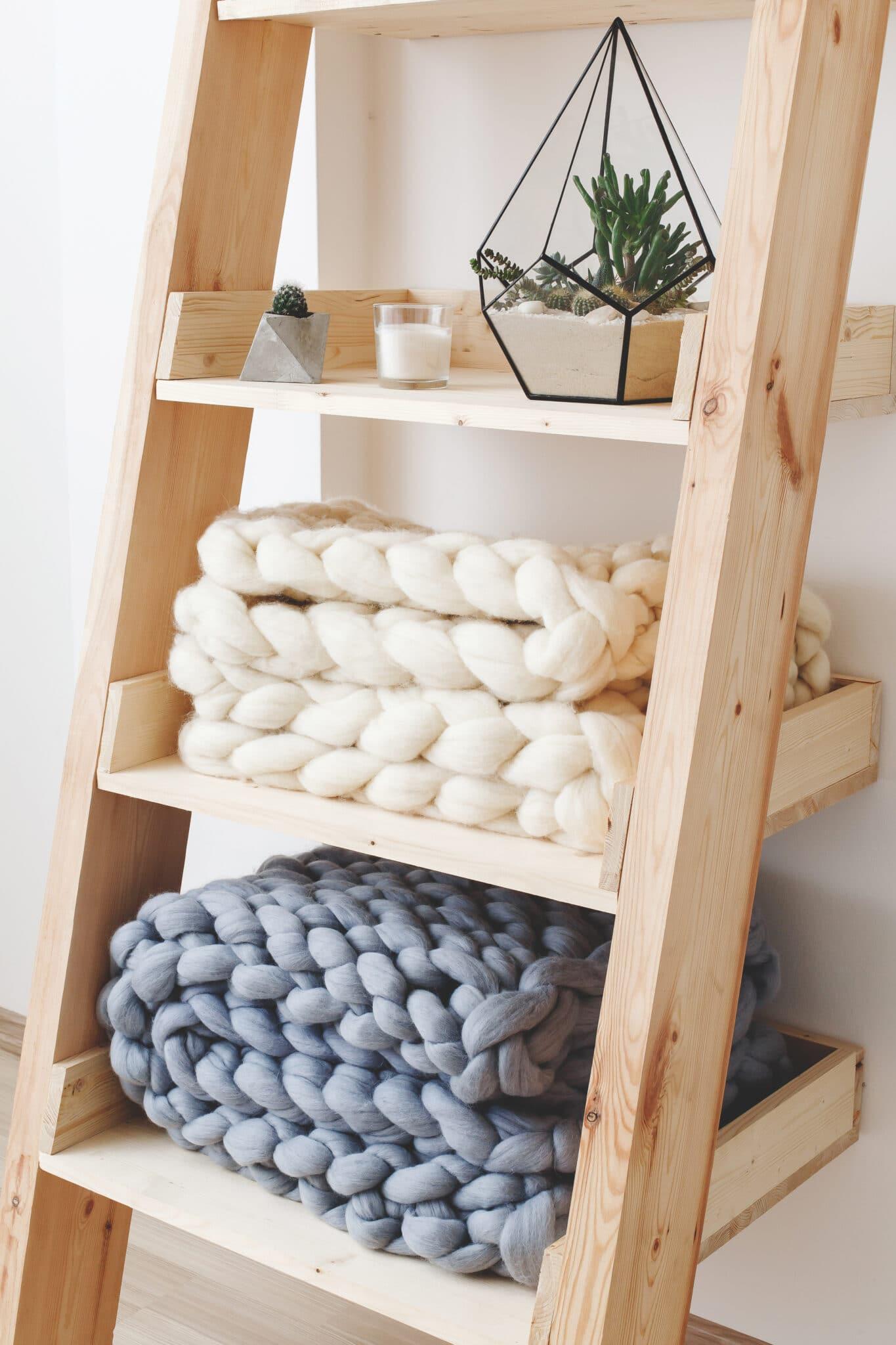 Uma prateleira de escada sendo usada como uma ideia de armazenamento de cobertor.