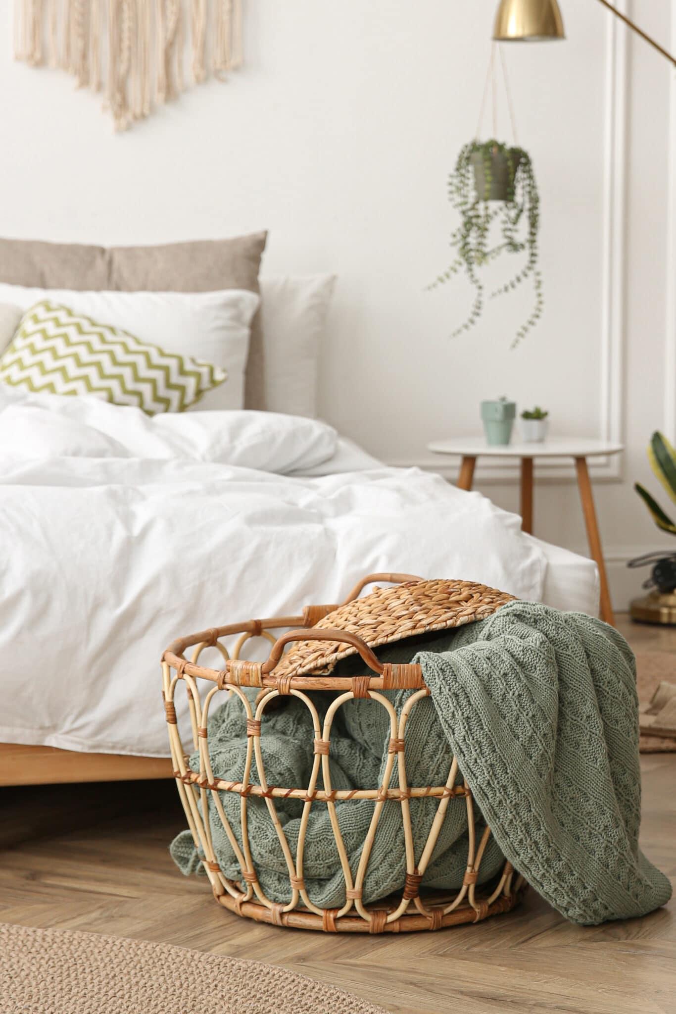 Uma cesta de vime sendo usada para armazenar cobertores em um quarto.