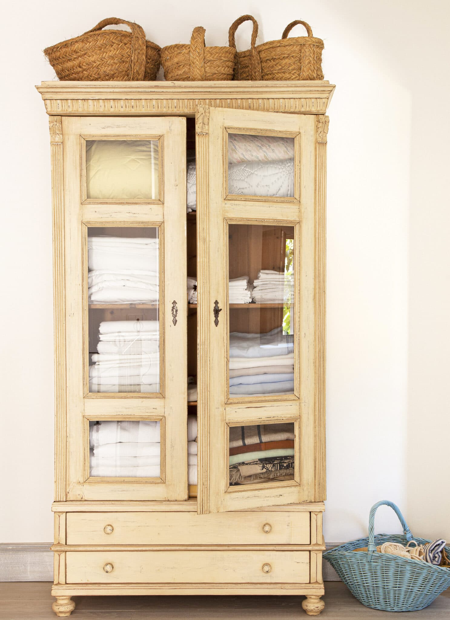Um armário de linho antigo com portas de janela, cheio de cobertores e lençóis empilhados.