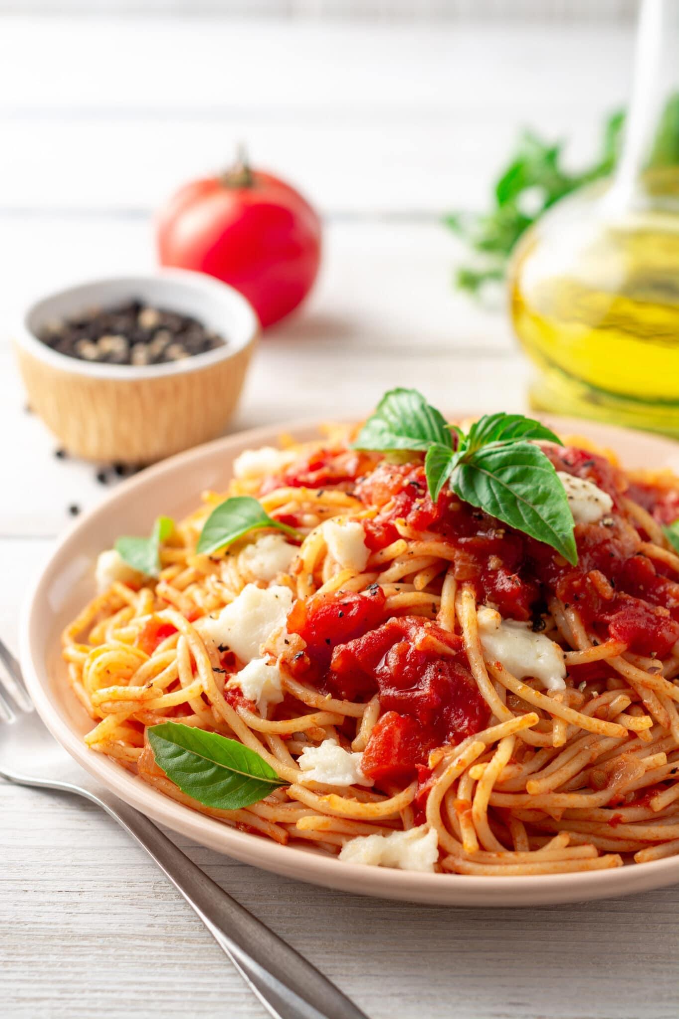 Spaghetti-Nudeln mit Tomatensauce, Mozzarella-Käse und frischem Basilikum in der Platte auf weißem Holzhintergrund.  Selektiver Fokus.