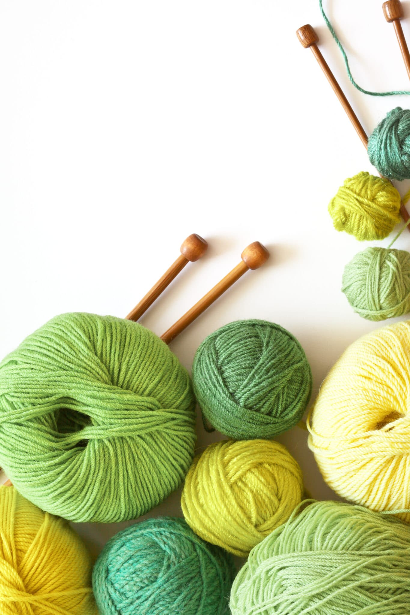 Knitting, needlework and hobbies. Green and yellow balls of yarn for hand knitting and wooden needles on a white background. Empty space for text. Flat lay, close up, macro.