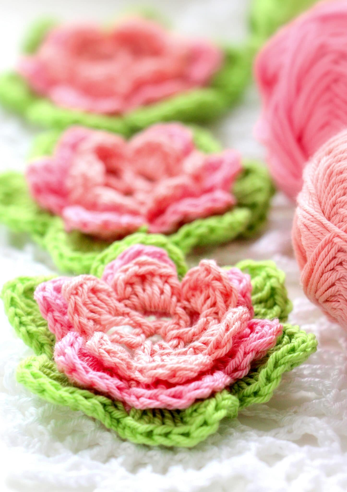 Crochet pink roses with green leaves against a bright white background.