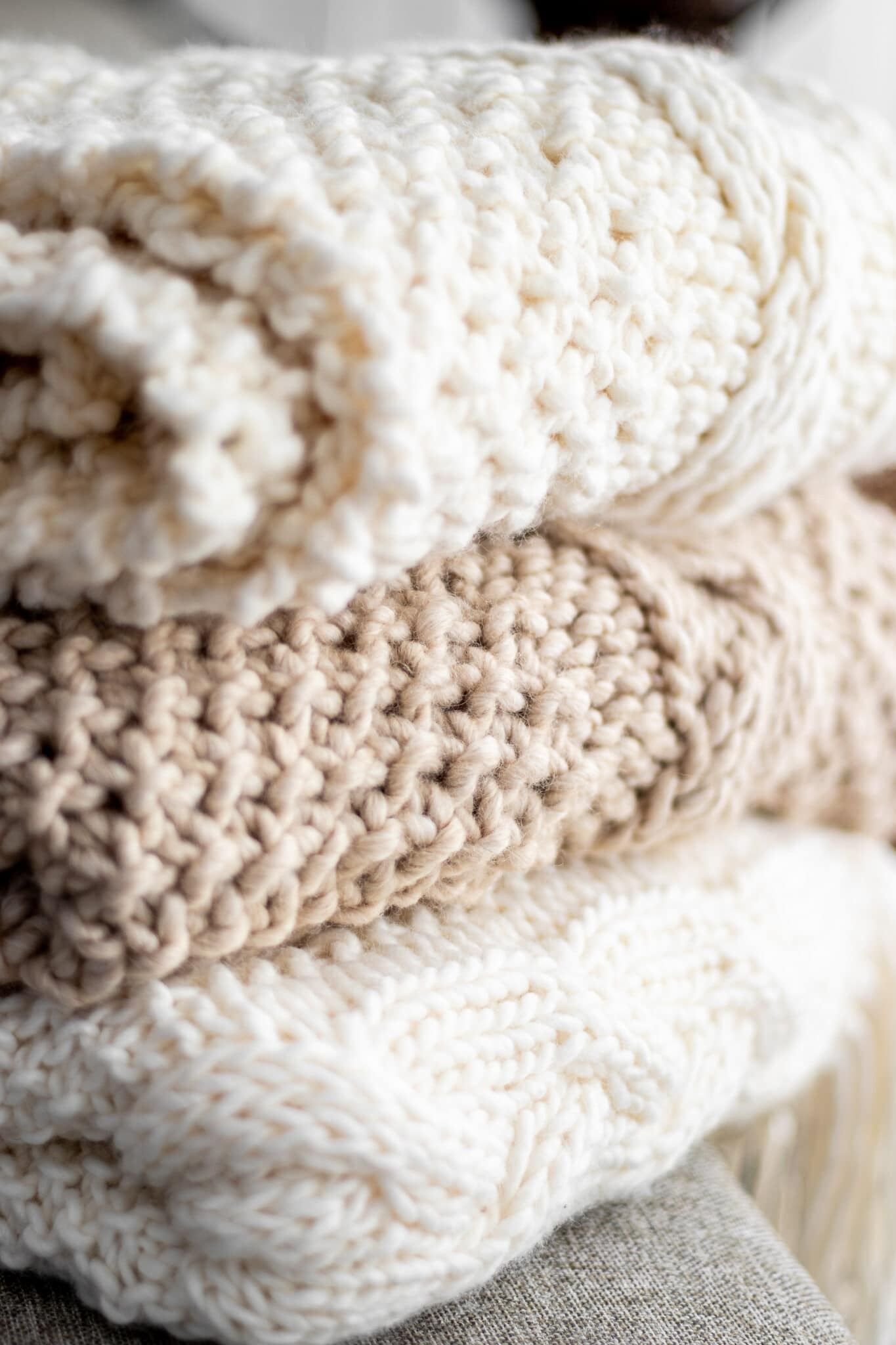 Beautiful hand knit and crocheted blankets in natural hues folded and stacked on top of one another.